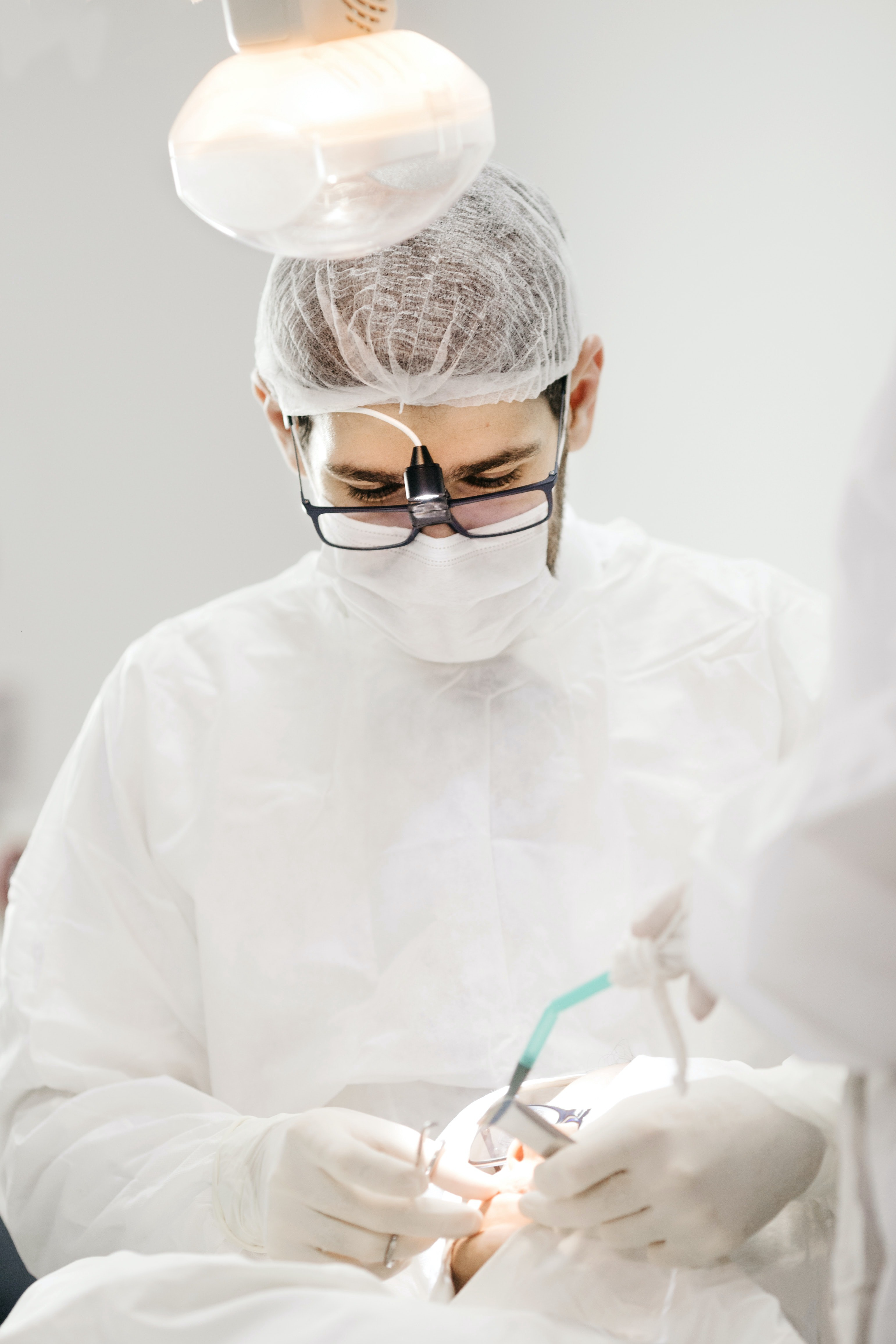 surgeon performing an operation in white gown and mask