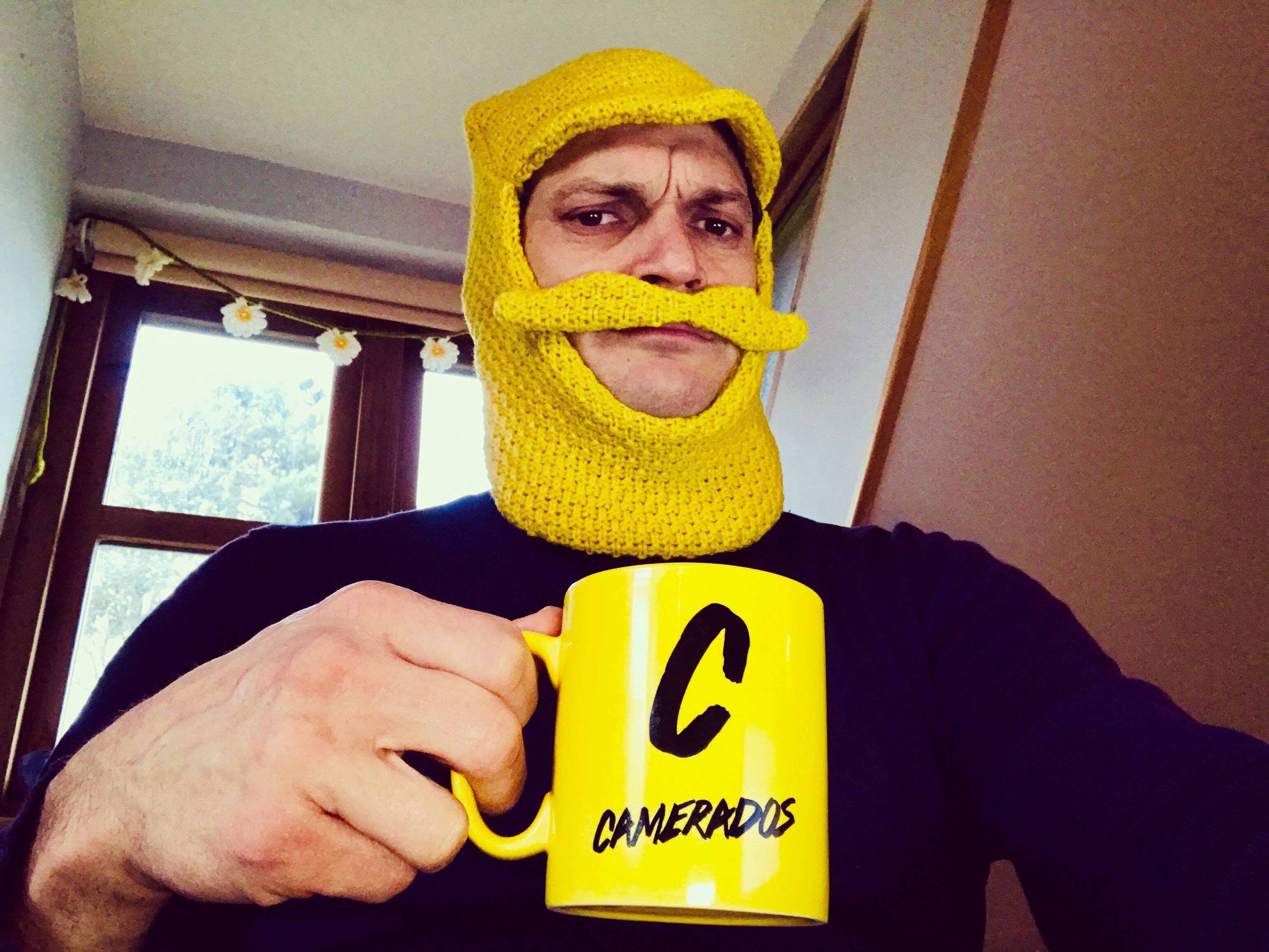 A man wearing a yellow hat that has a moustache holds up a yellow mug that has 'Camerados' on it.