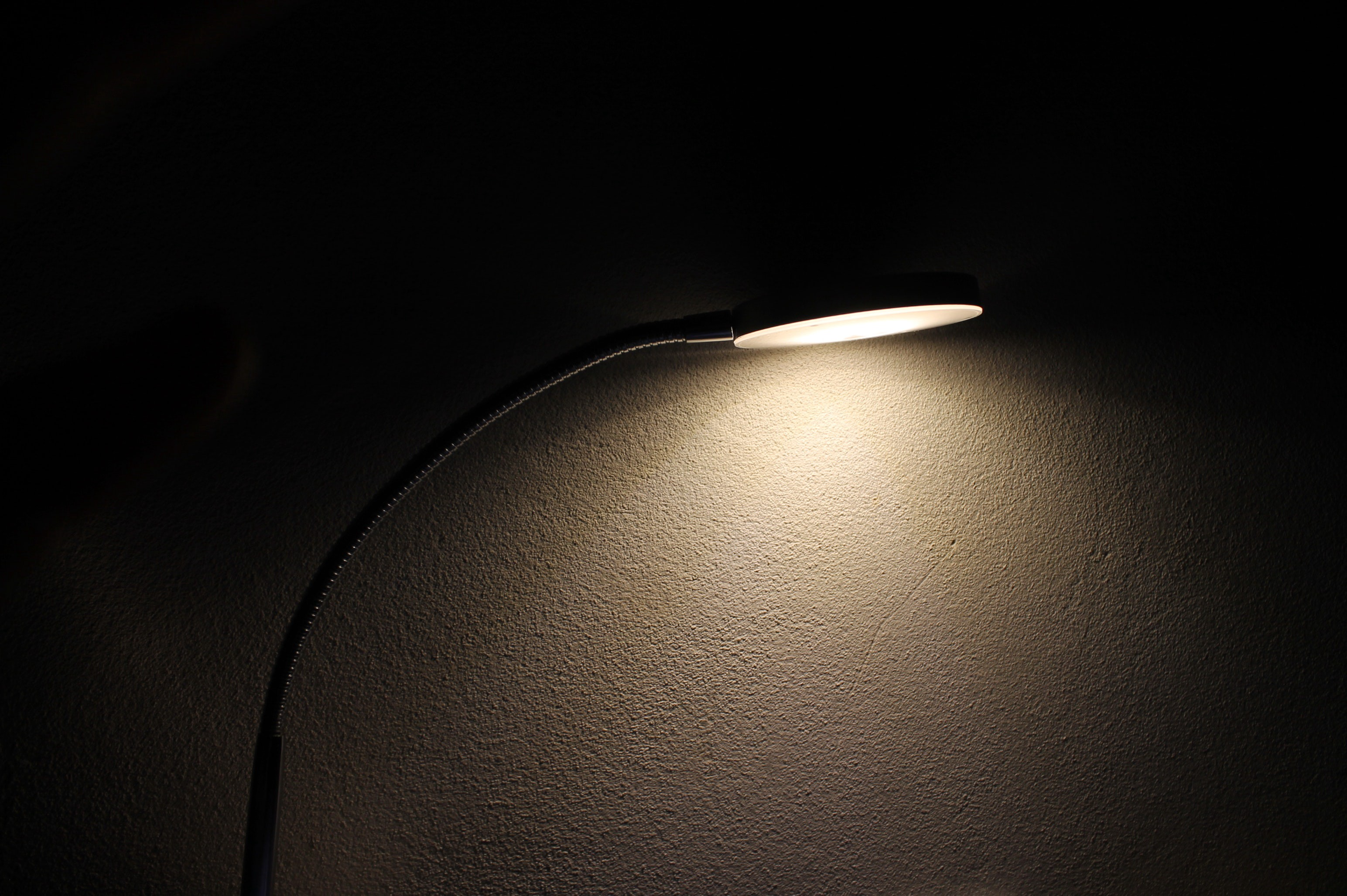 Photo of a gold desk lamp, turned on.