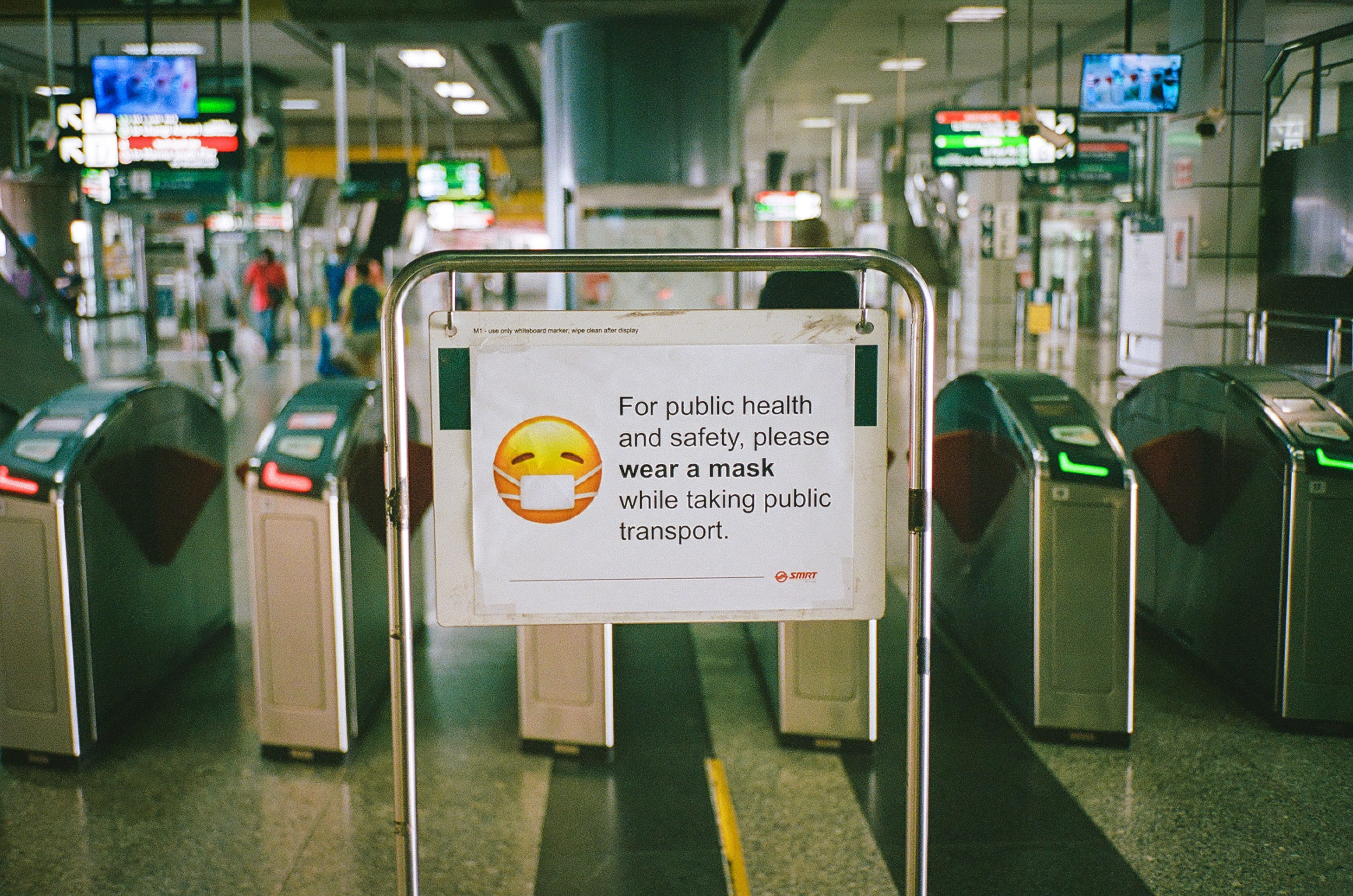 Image of subway station turn styles with sign asking for patrons to wear mask on public transportation