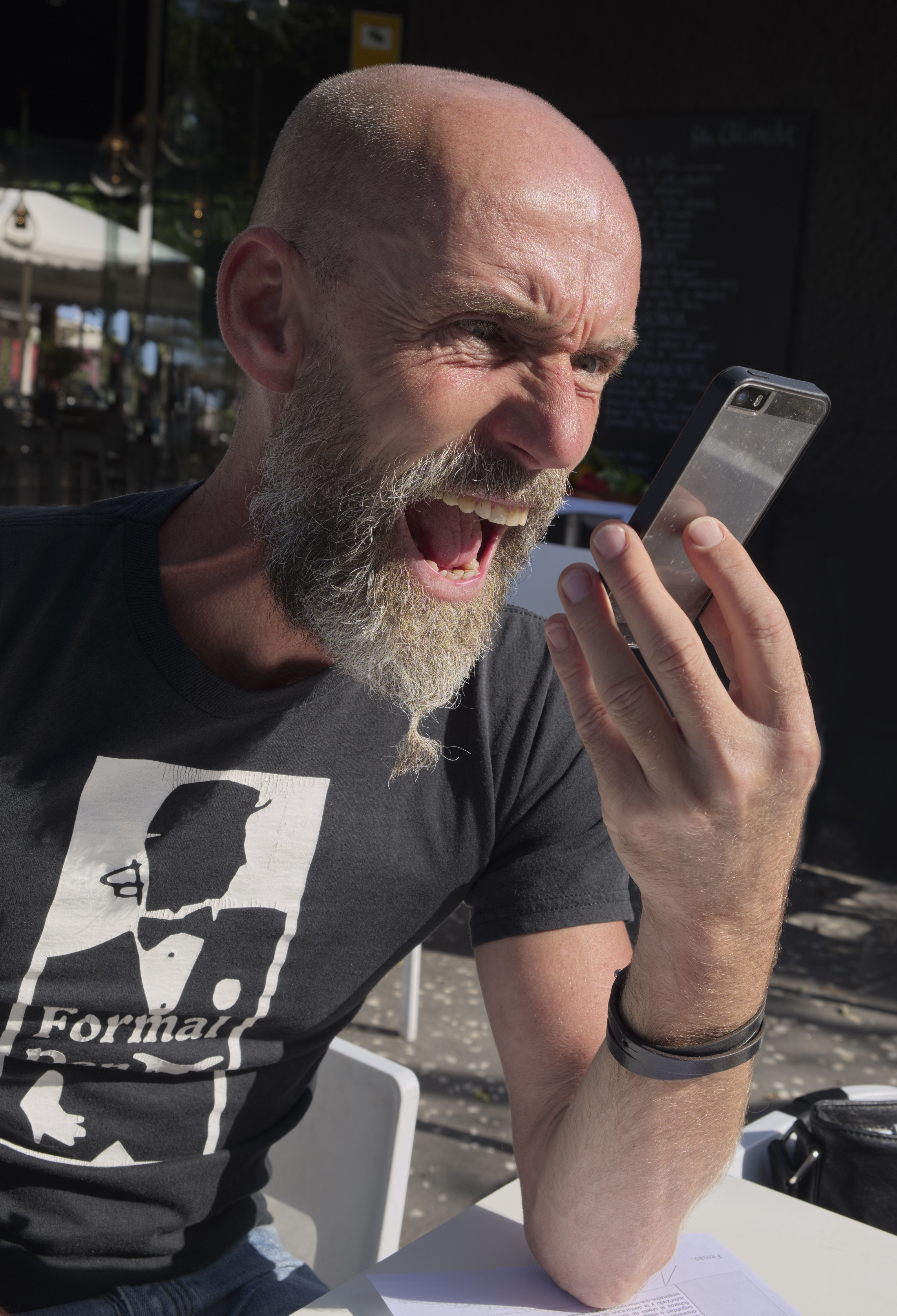 An angry looking bearded man shouts into his phone