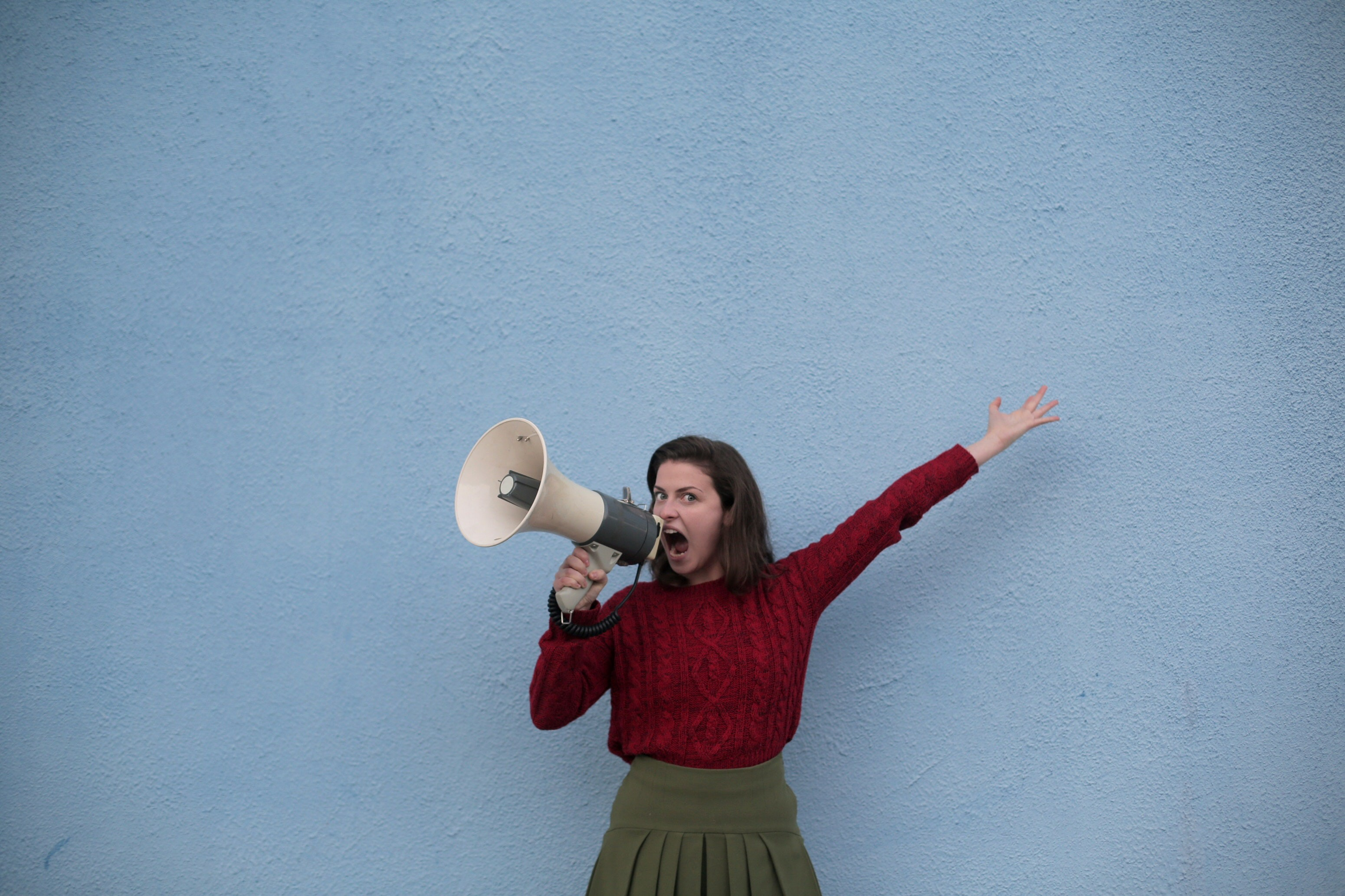 Woman with a bullhorn. How to Write Headlines People Will Click On.