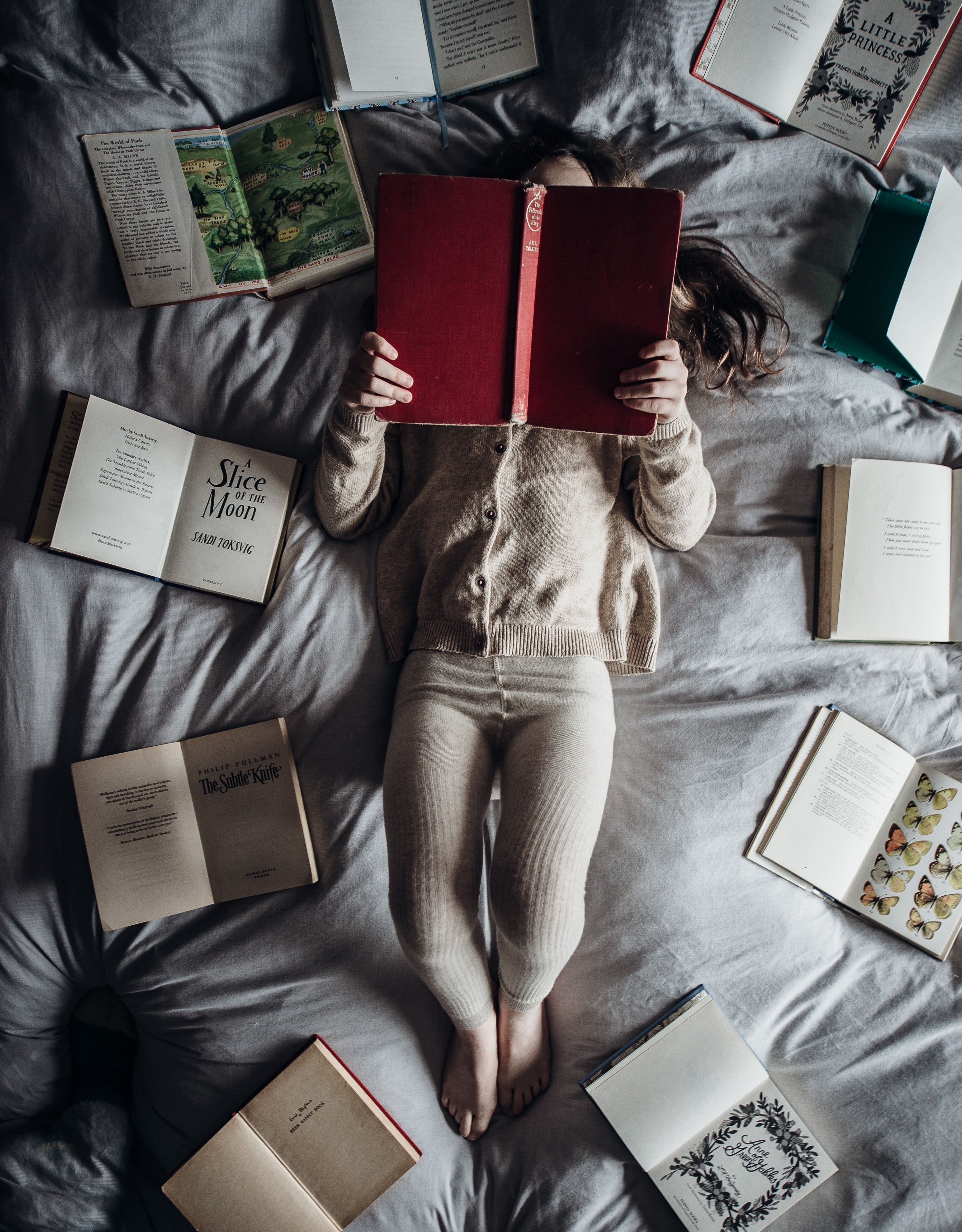 a child reading a book in bed surrounded by books