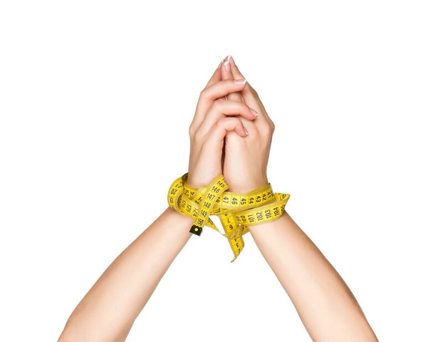 A pair of hands tied up with measuring tape.
