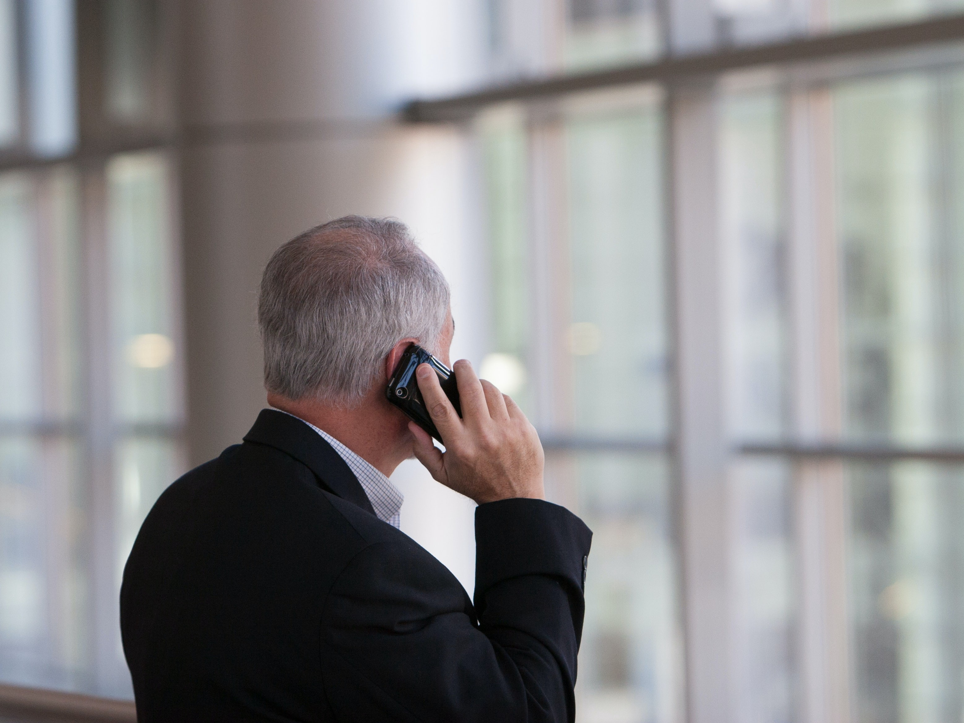 A grey-haired man in a suit talks on telephone.