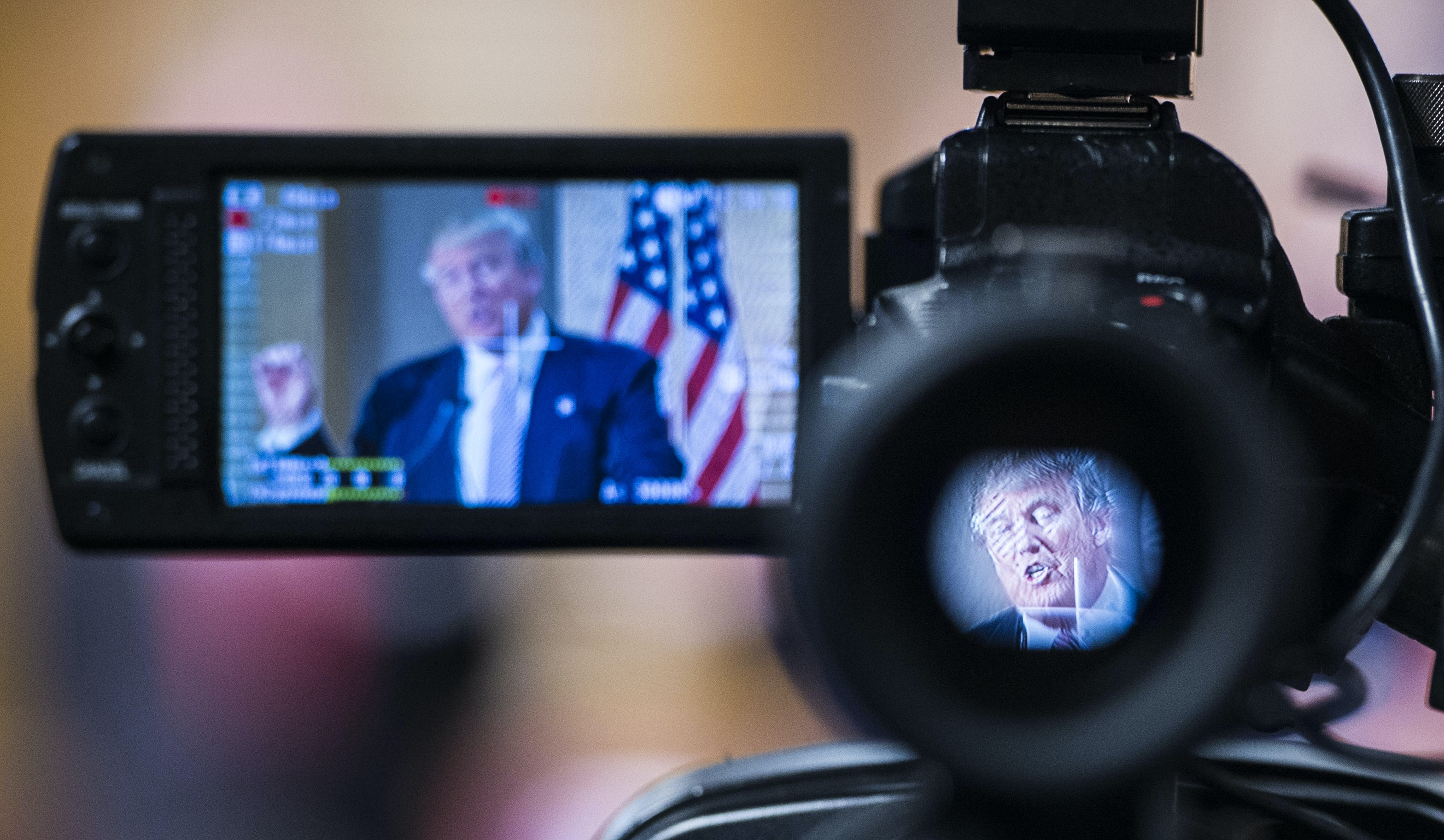 Donald Trump is seen speaking through a camera at a press conference.