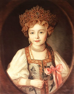 Alexandra Pavlovna wearing a very large pearl-studded kokoshnik over a lacy cap, sarafan, and white blouse.