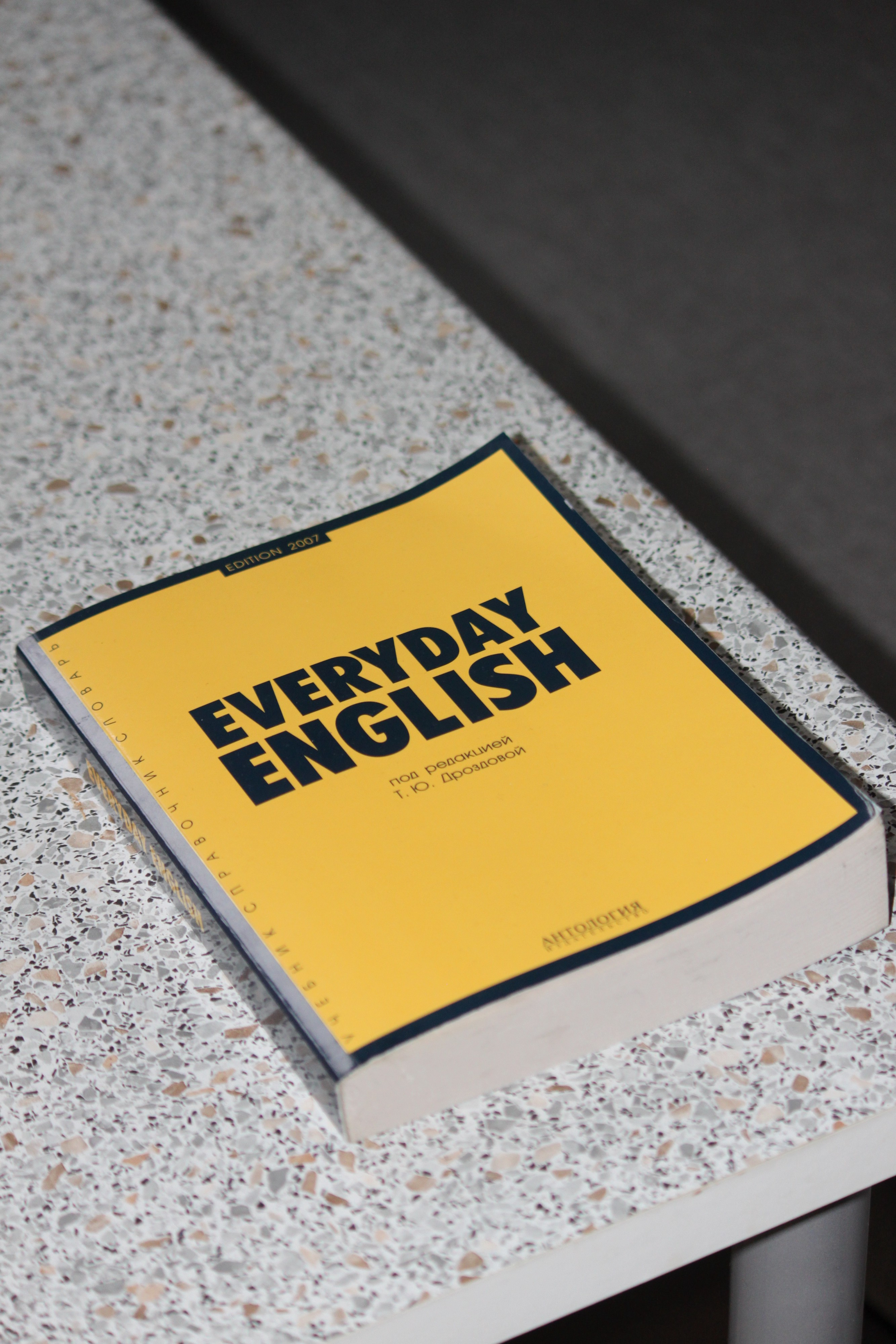 """Image of a yellow book titled, """"Everyday English"""" on top of a table."""