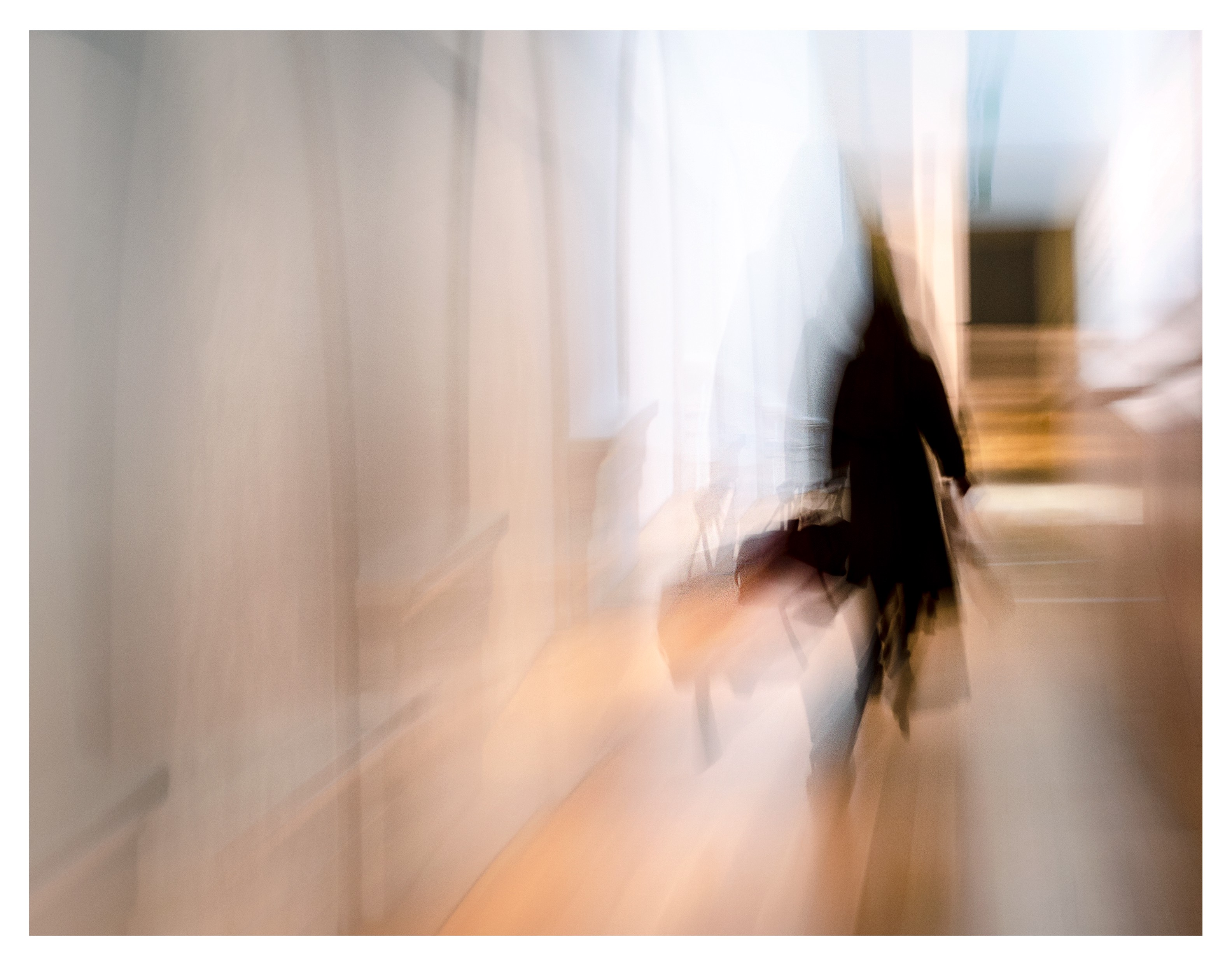 Blurred image of a person carrying a briefcase walking away