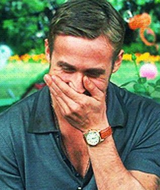 Ryan Gosling giggling with his hand over his mouth.