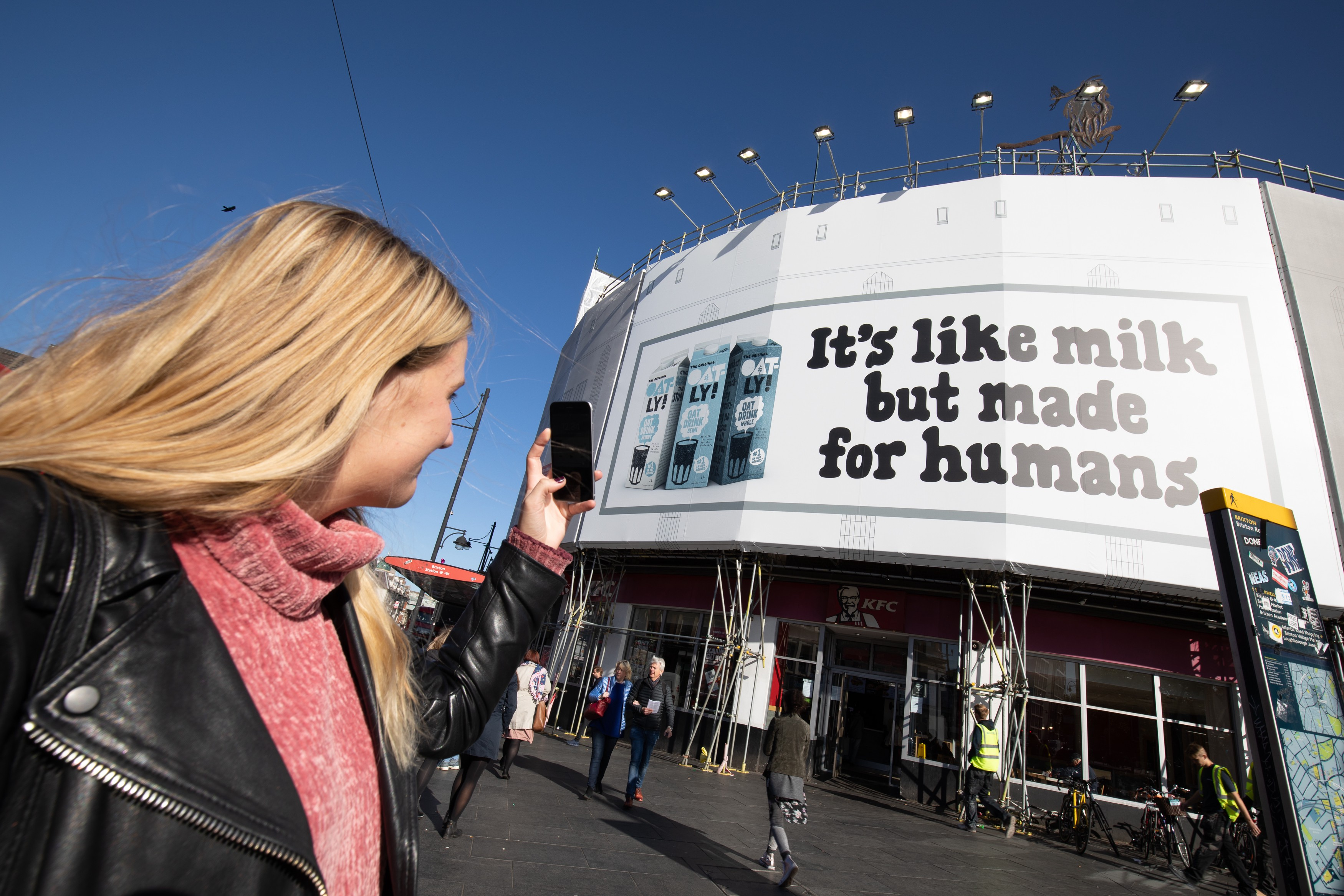 """Woman takes a picture of a advert which reads """"It's like milk but made for humans."""""""