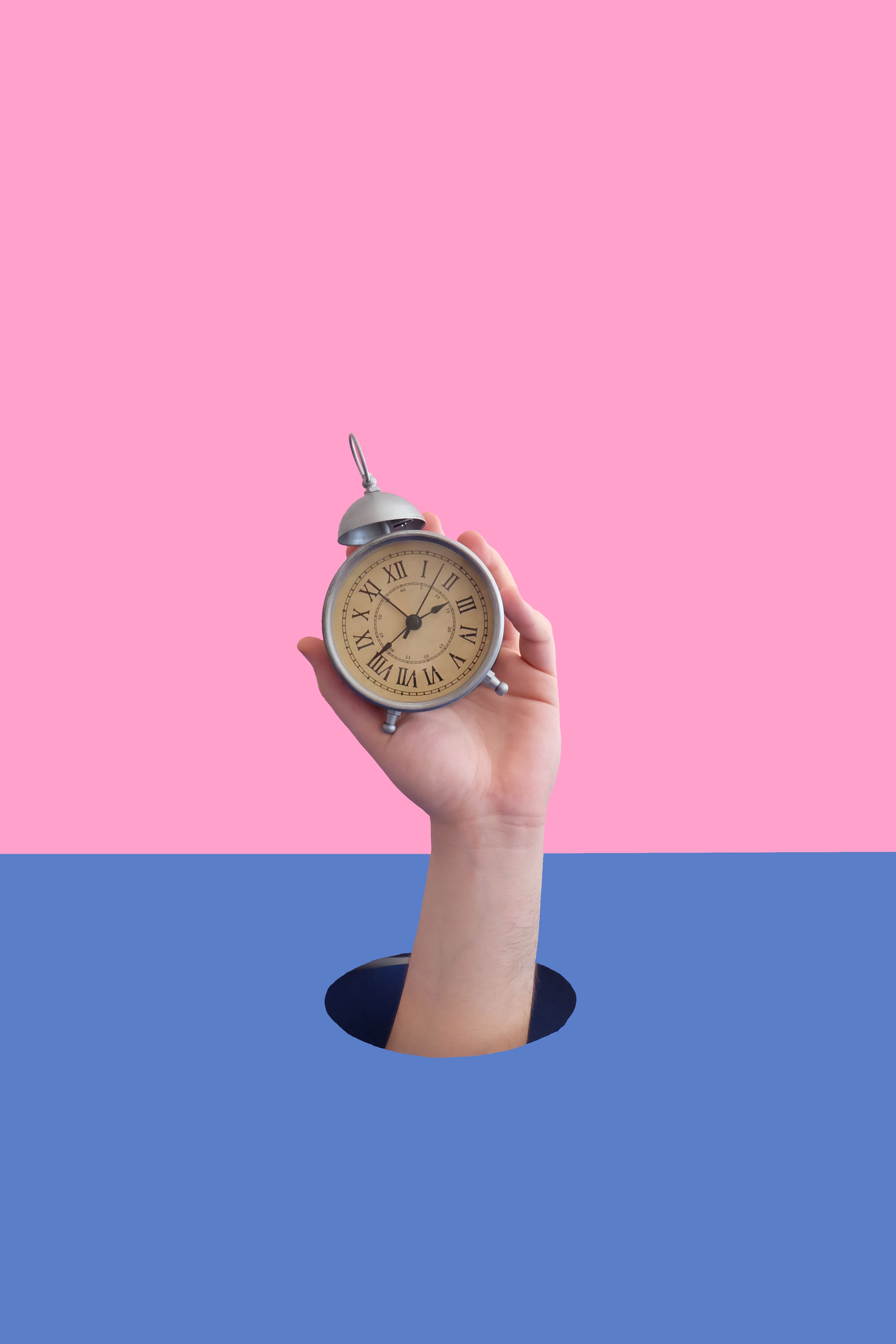 an arm holding an old clock against a blue and pink backdrop