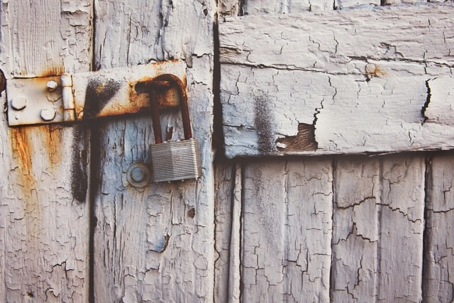 A photo with an old, rusty lock indicating lack of safety. Photo by Tim Mossholder on Unsplash
