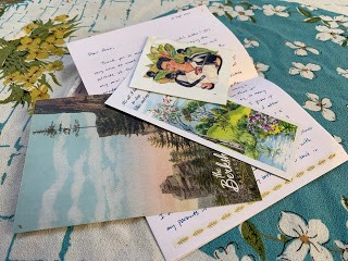 On a white and turquoise tablecloth, my first letter is laid out. It includes a postcard of mountains, a bookmark of green fields and a Frida Kahlo transfer.