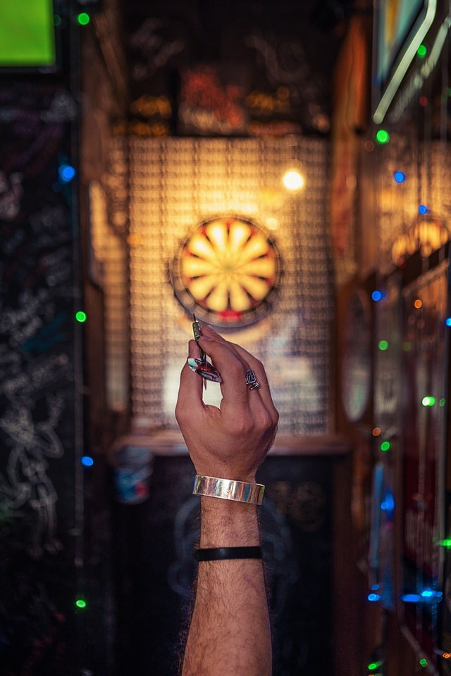 A first PoV photo of someone holding a dart and aiming for a bullseye ahead—Photo by Ameer Basheer on Unsplash