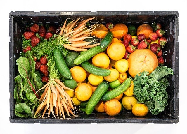 Box full of various fruits and vegetables.