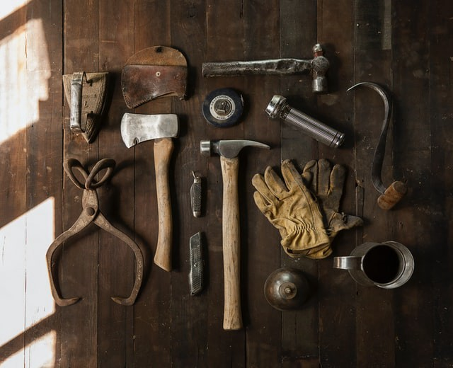 Old looking tools (hammers, an axe, gloves, etc.)—Photo by Heather Zabriskie on Unsplash