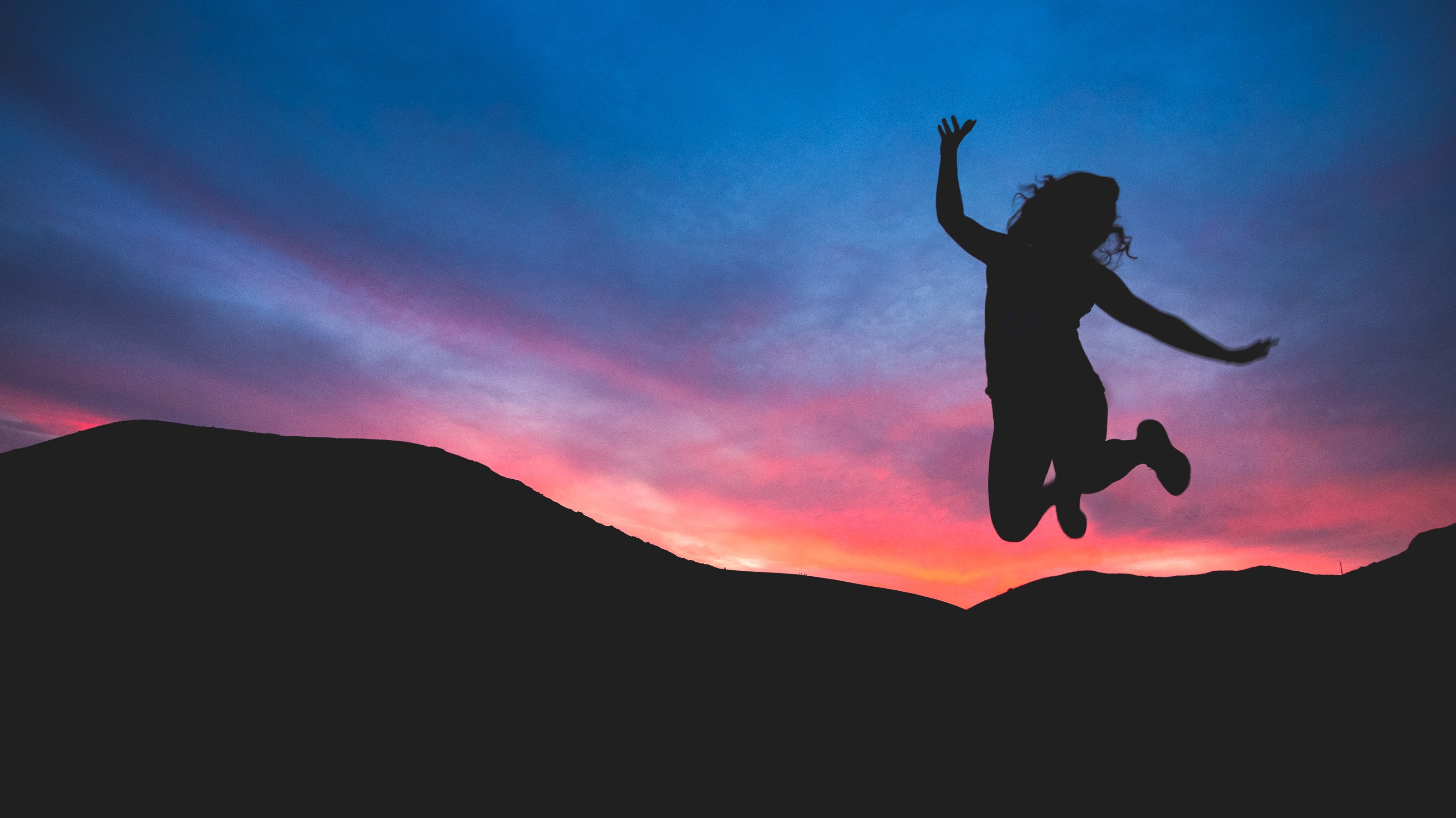 a person jumping high on a hill with a sunset in the background
