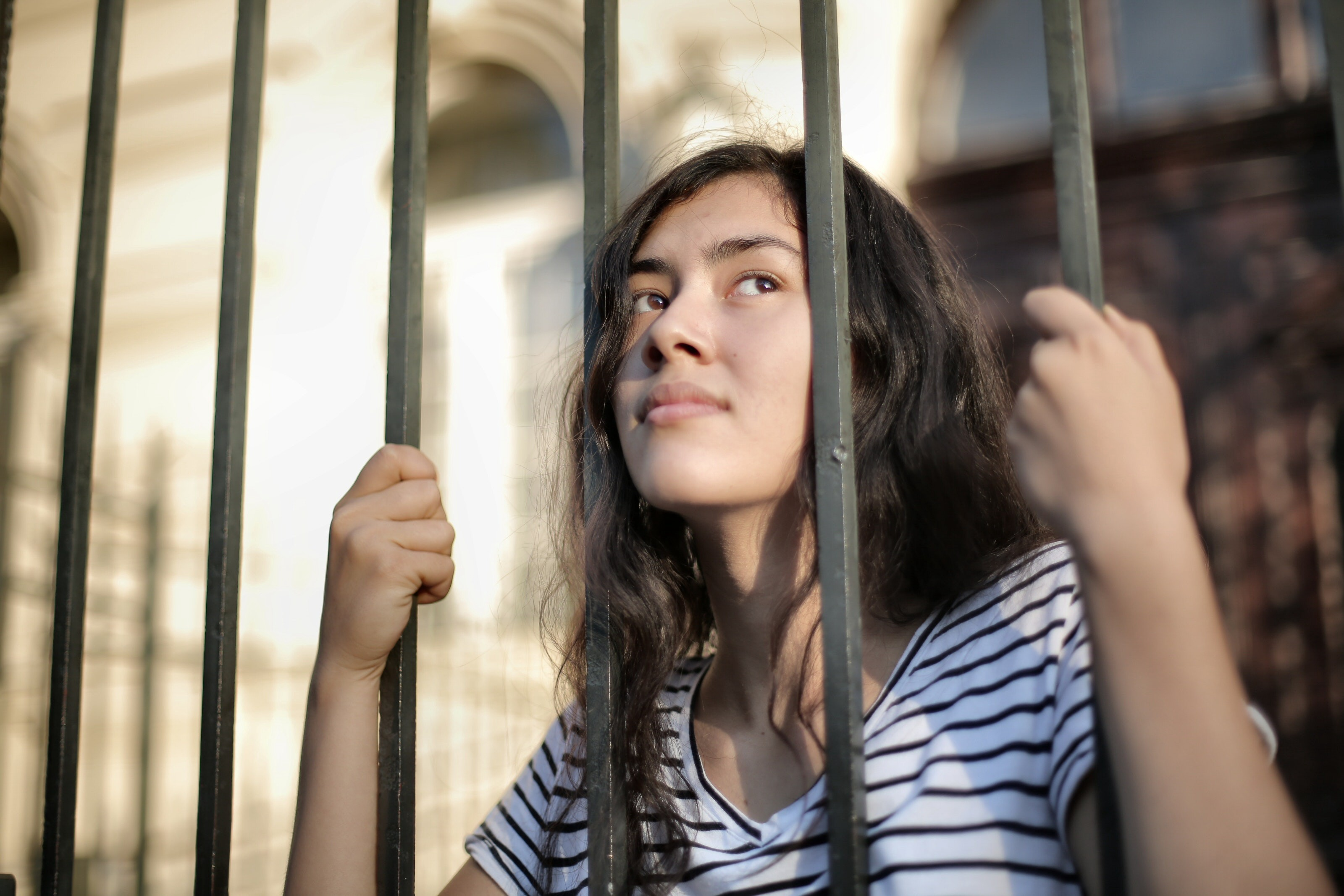 Young woman trapped behind prison bars