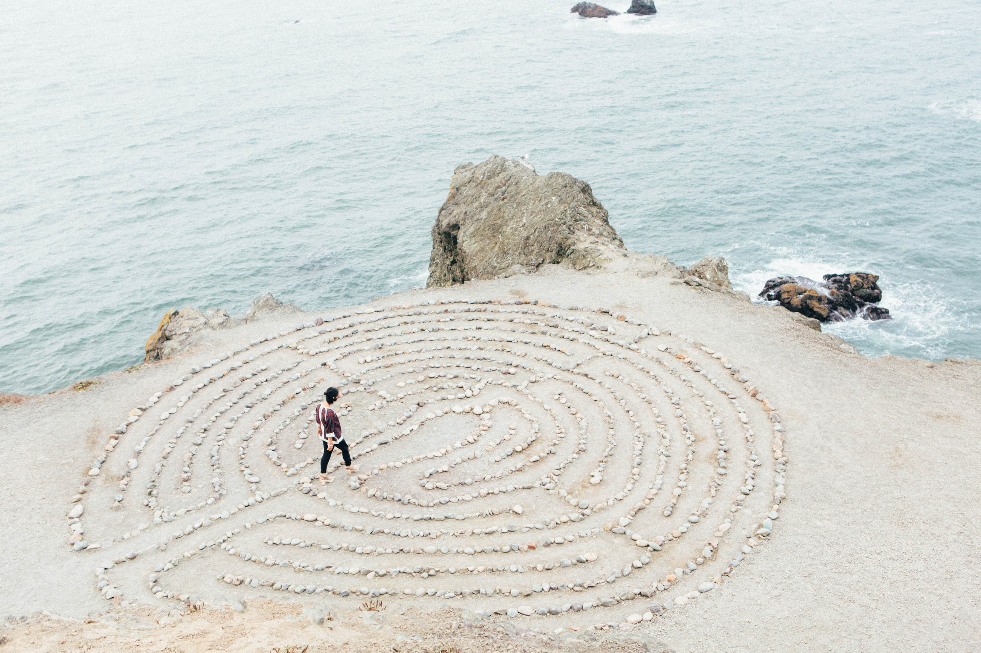 On a sandy patch of rocky coastline, a woman walks through a pattern of stones on the ground laid out like a labyrinth.