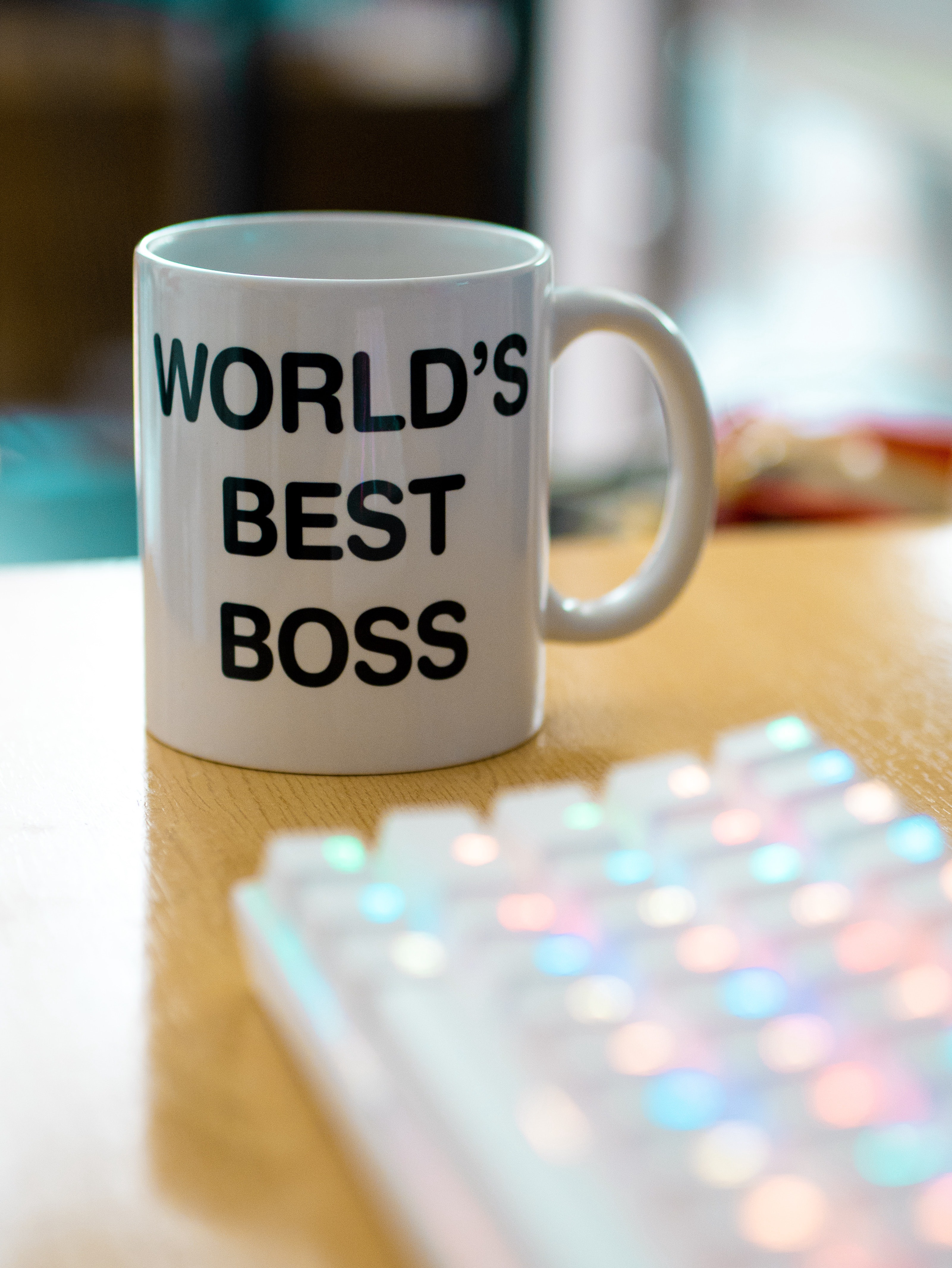 "Coffee mug next to computer keyboard that says ""World's Best Boss"""