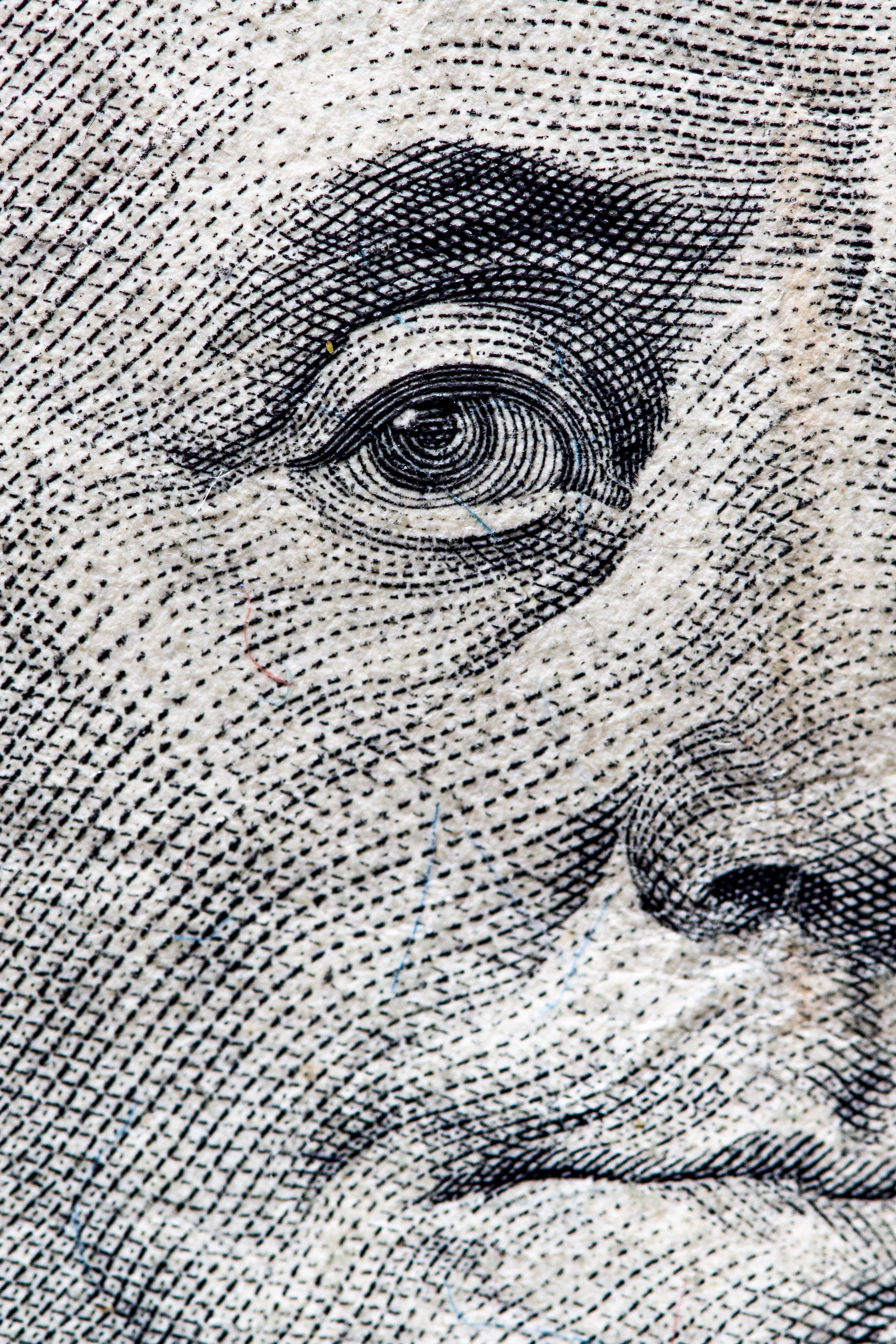 A close up of the image of Benjamin Franklin from a $100 bill