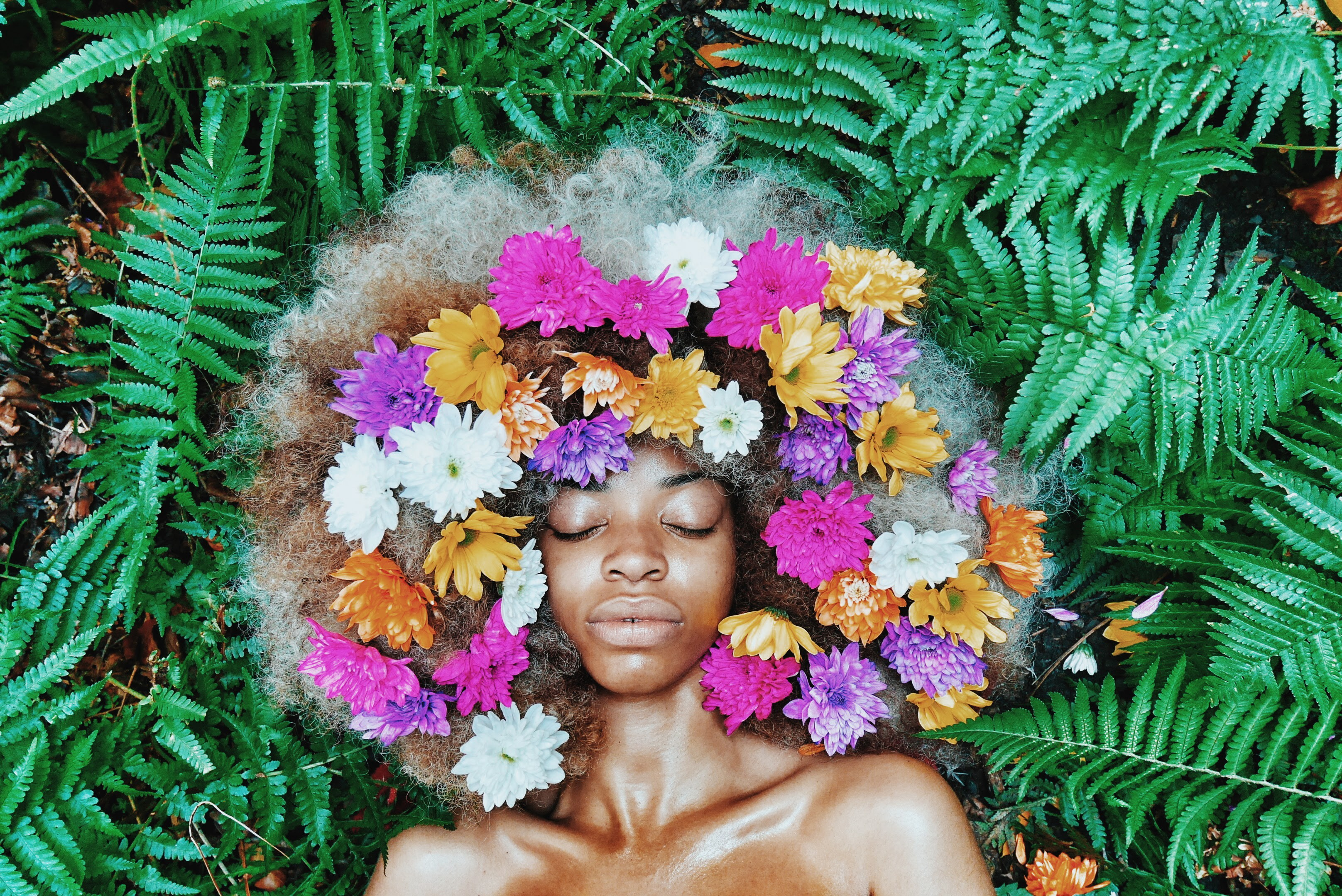 A photo of a Black woman with flowers in her hair against a leafy background.