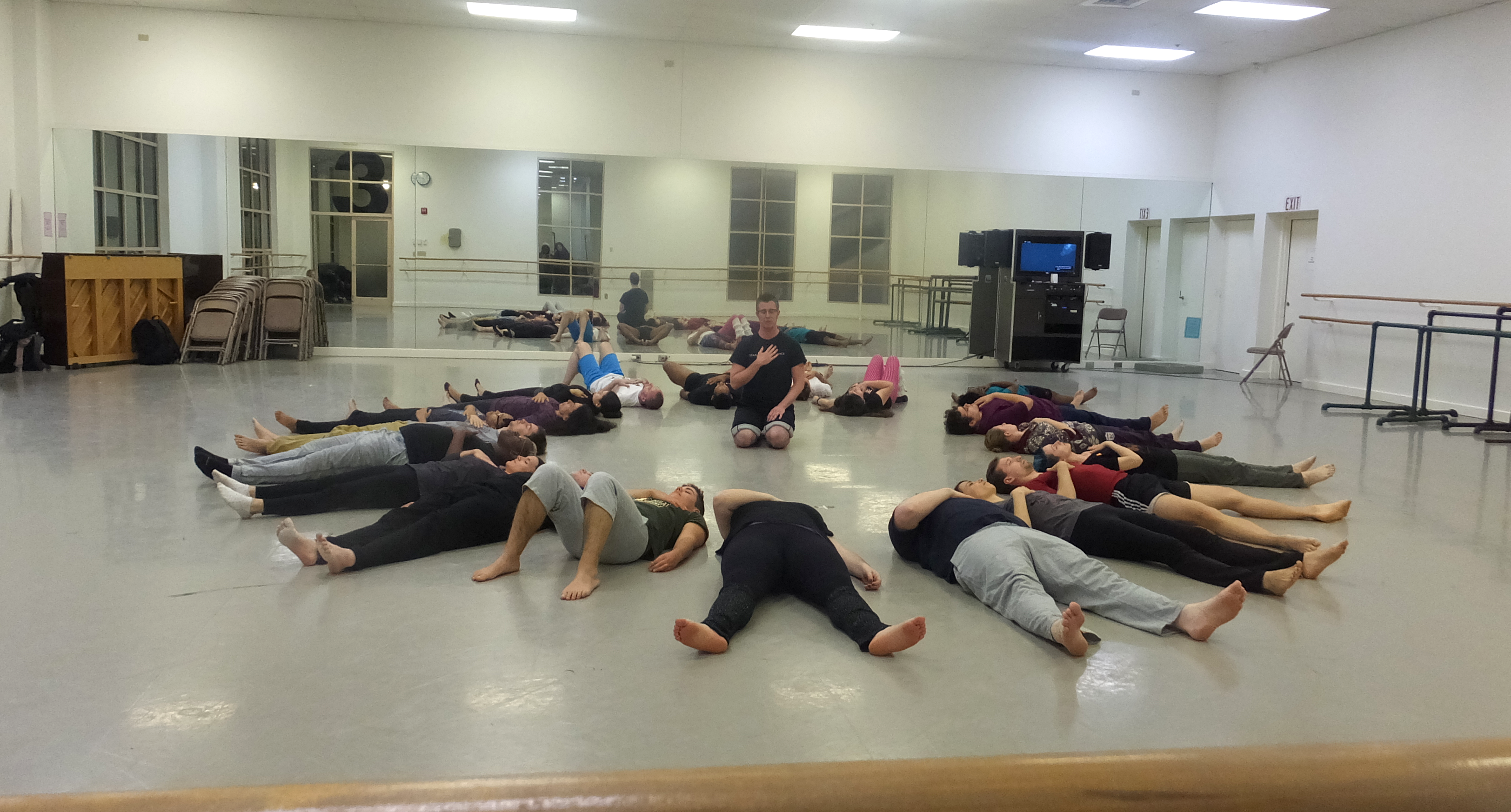 Group of people laying on their backs on the floor in a circle. Dorsey sits on his knees in the center with hand on heart.