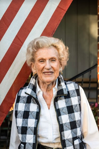 An elderly woman in a plaid vest standing in front of a US flag on a porch.