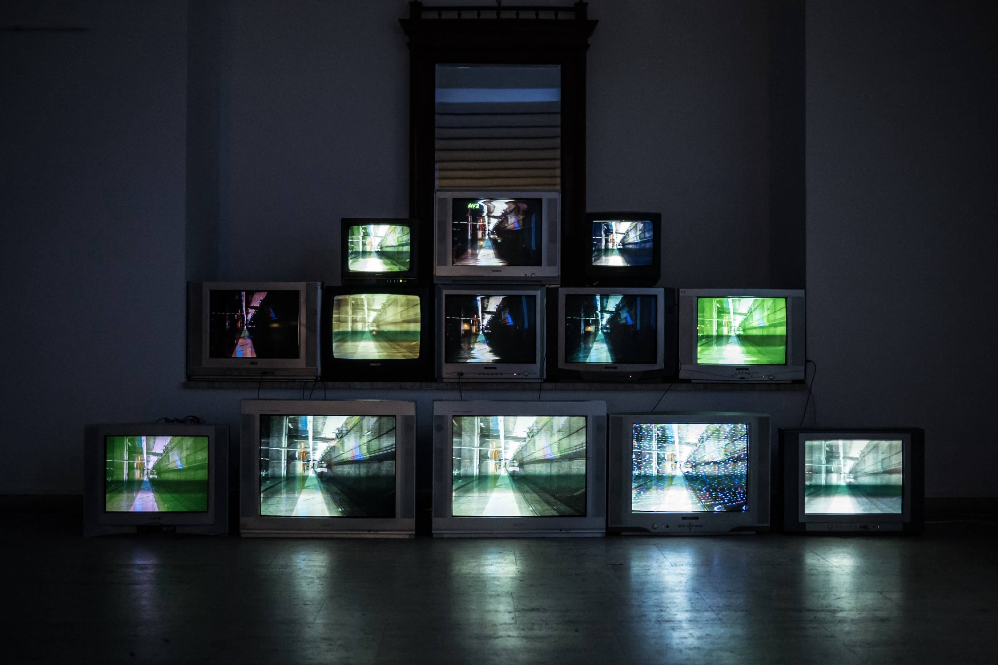 A row of televisions turned on in a dark room.