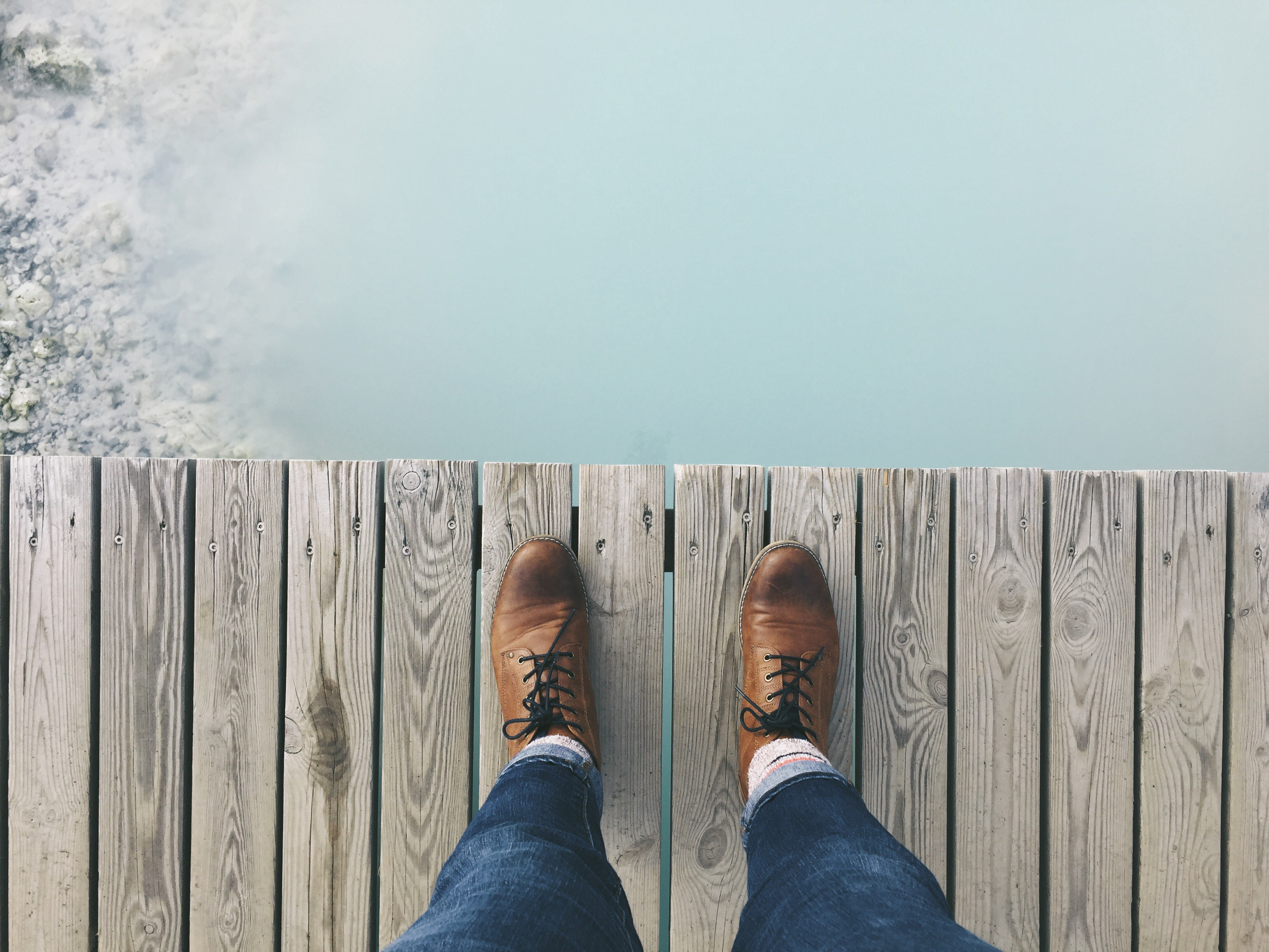 Person looking down at their shoes as they stand on wooden walkway over cloudy water.