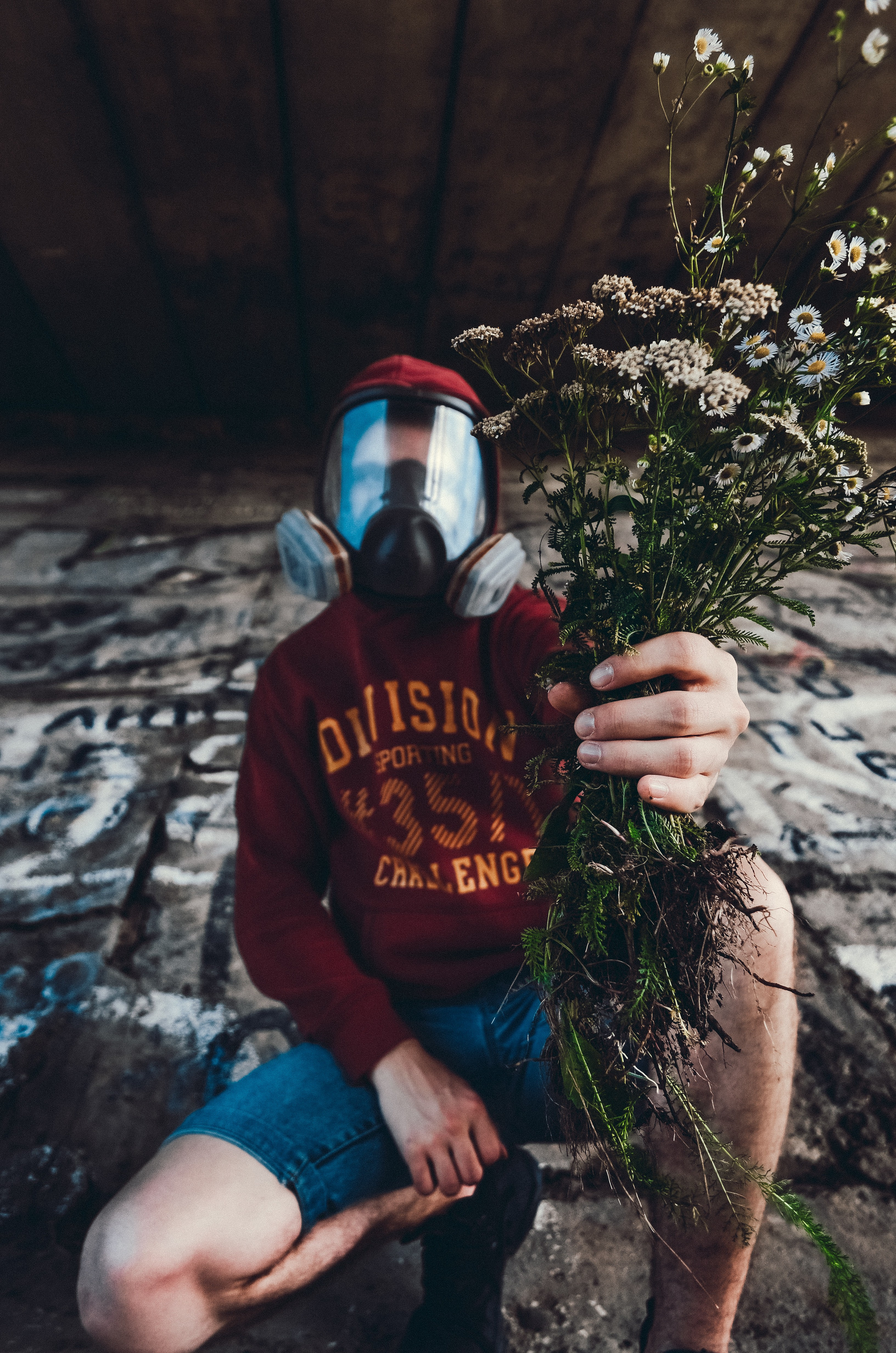Man wearing gas mask while holding dead flowers