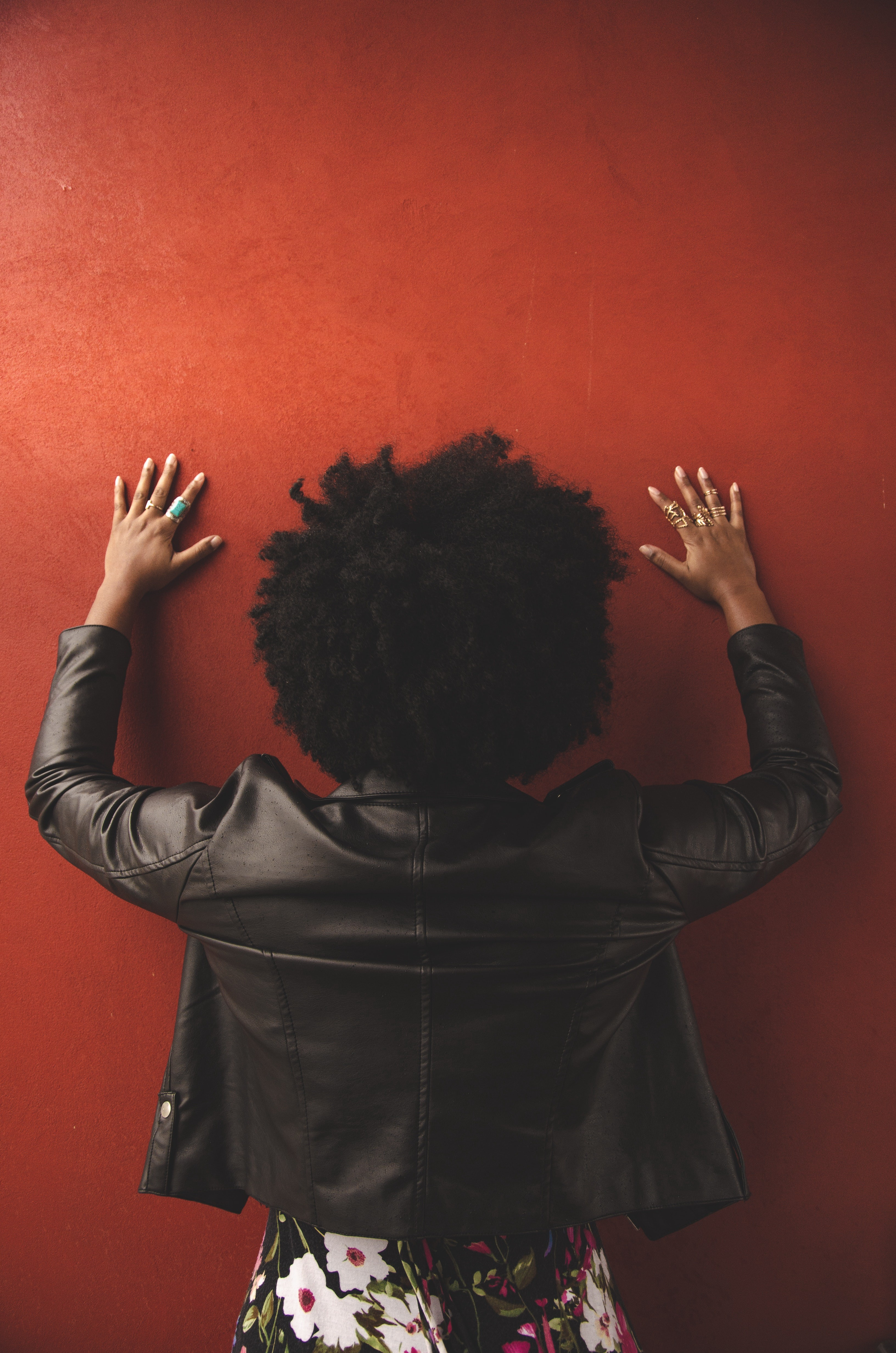 Image of a woman with afro hair taken from behind with hands up against the wall.