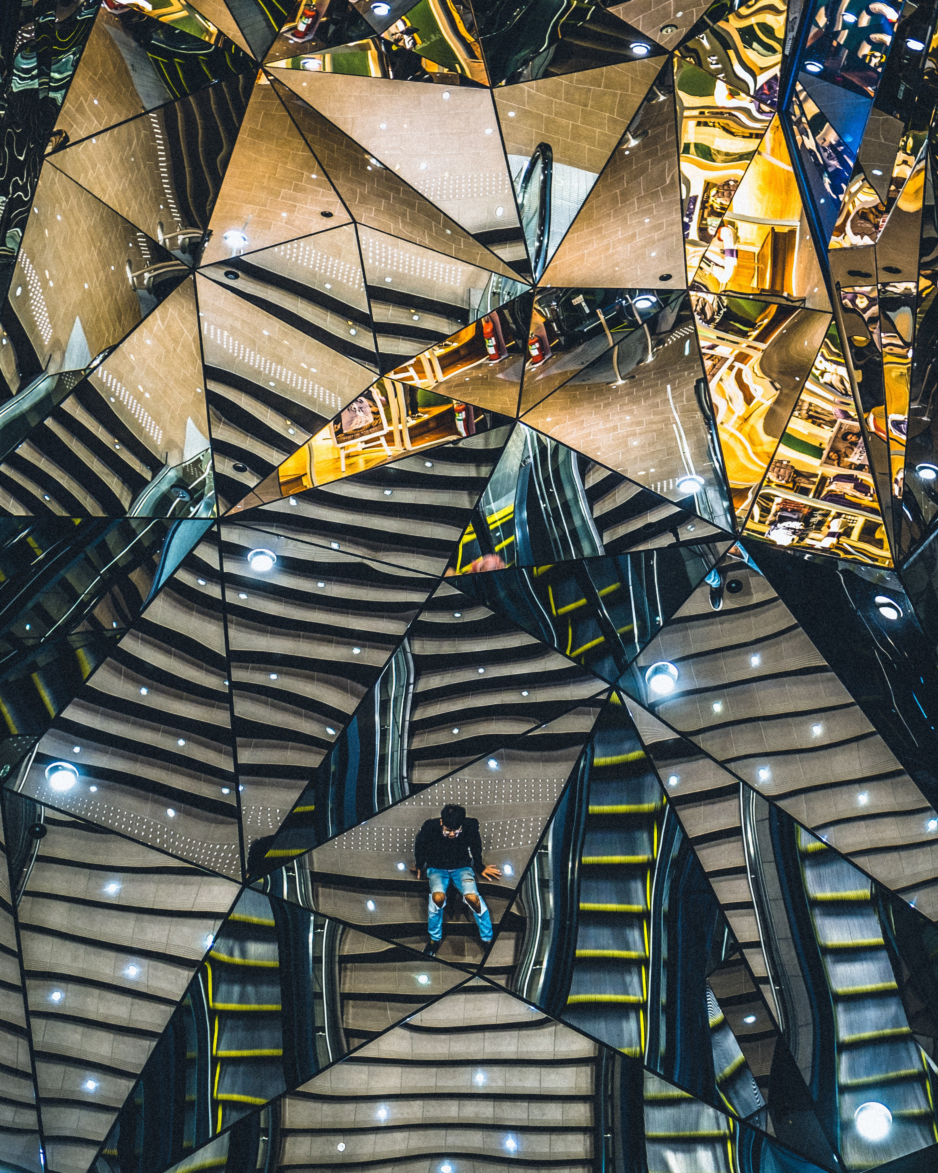 Mirror of geometric shapes, reflecting an abstracted set of stairs and benches with people on them.