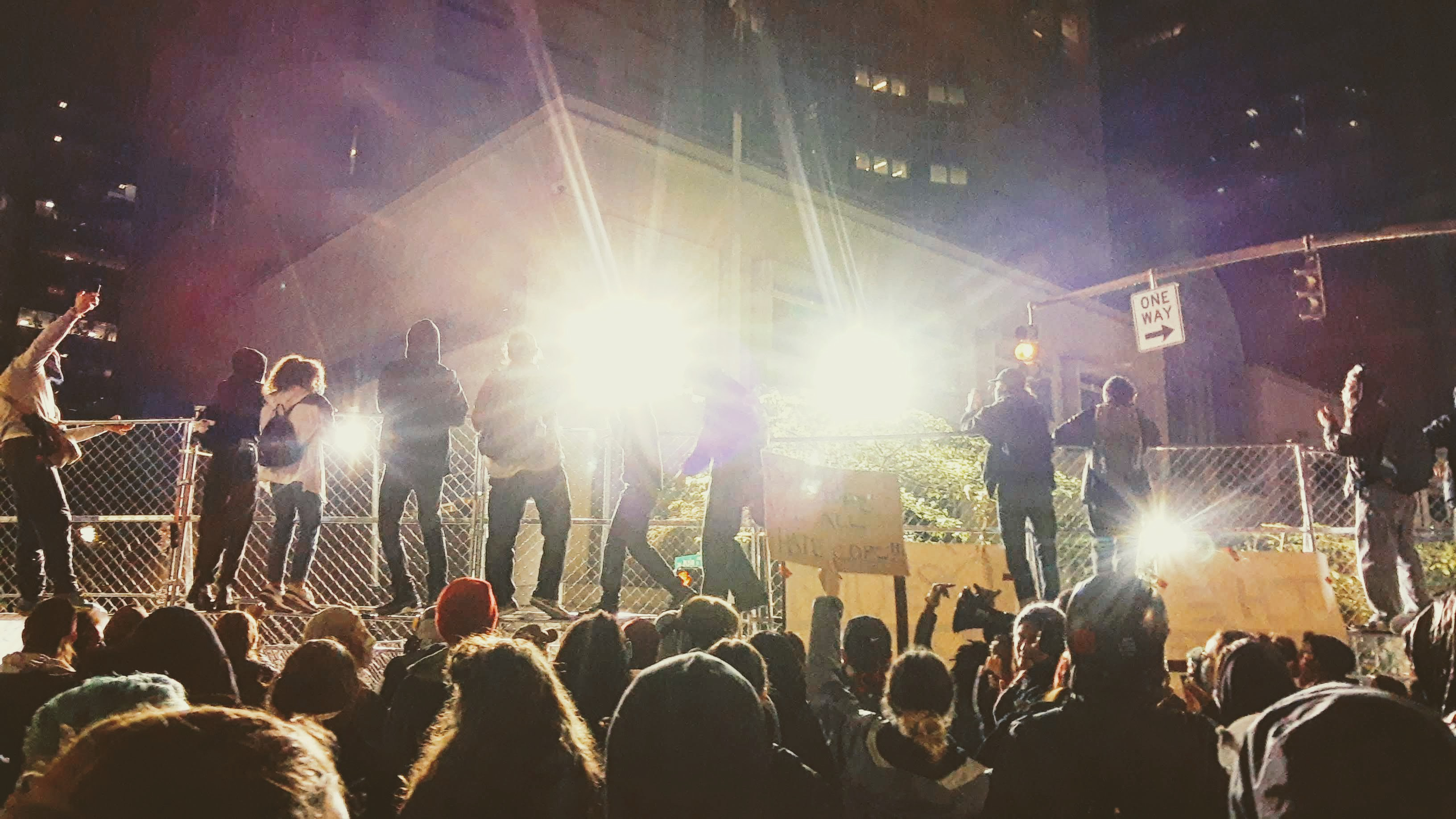 Protesters have climbed a fence; other protesters stand behind. Two spotlights shine directly into the camera
