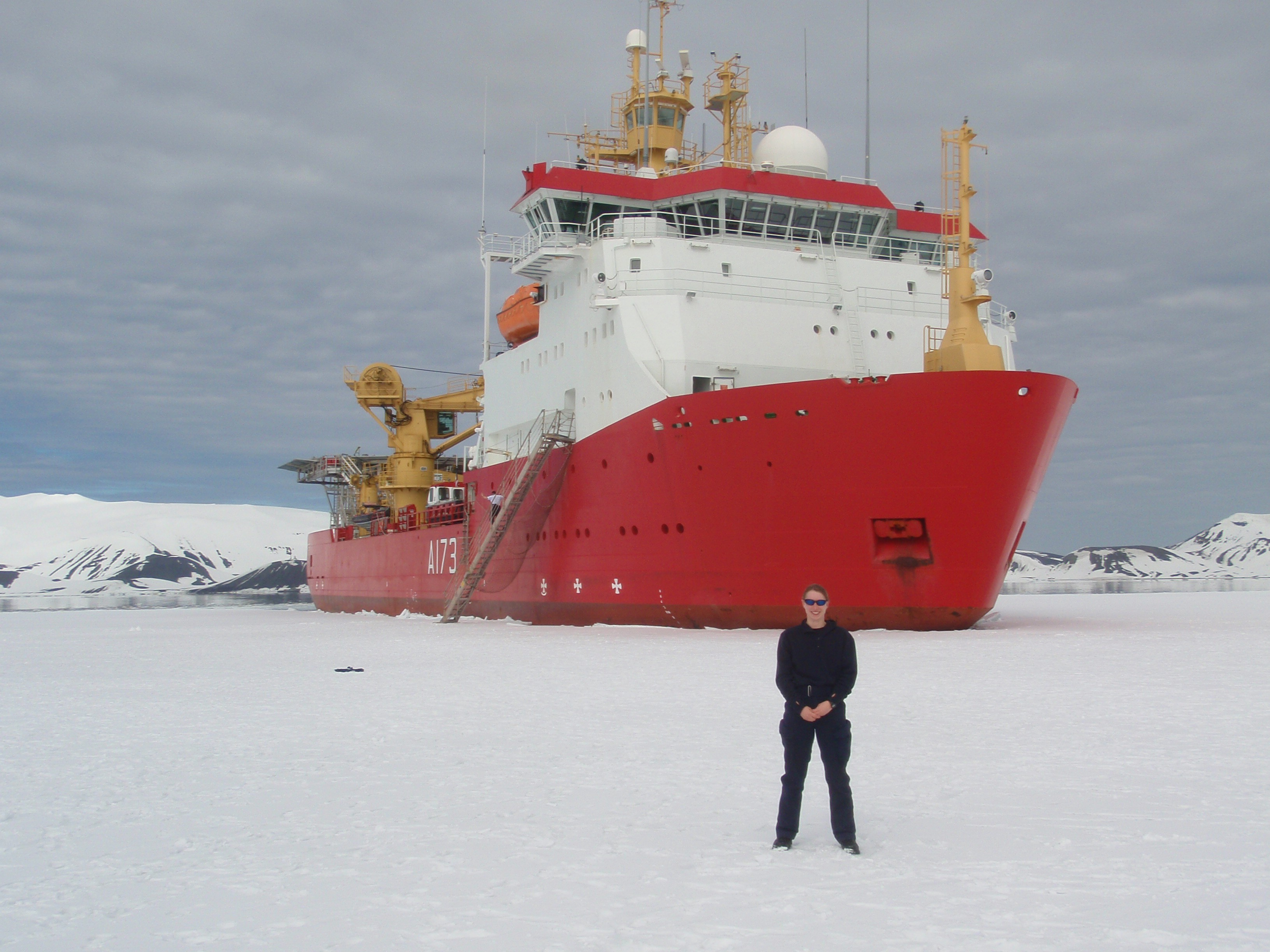 A woman stands in front of a red and white ship and a landscape of snow and ice