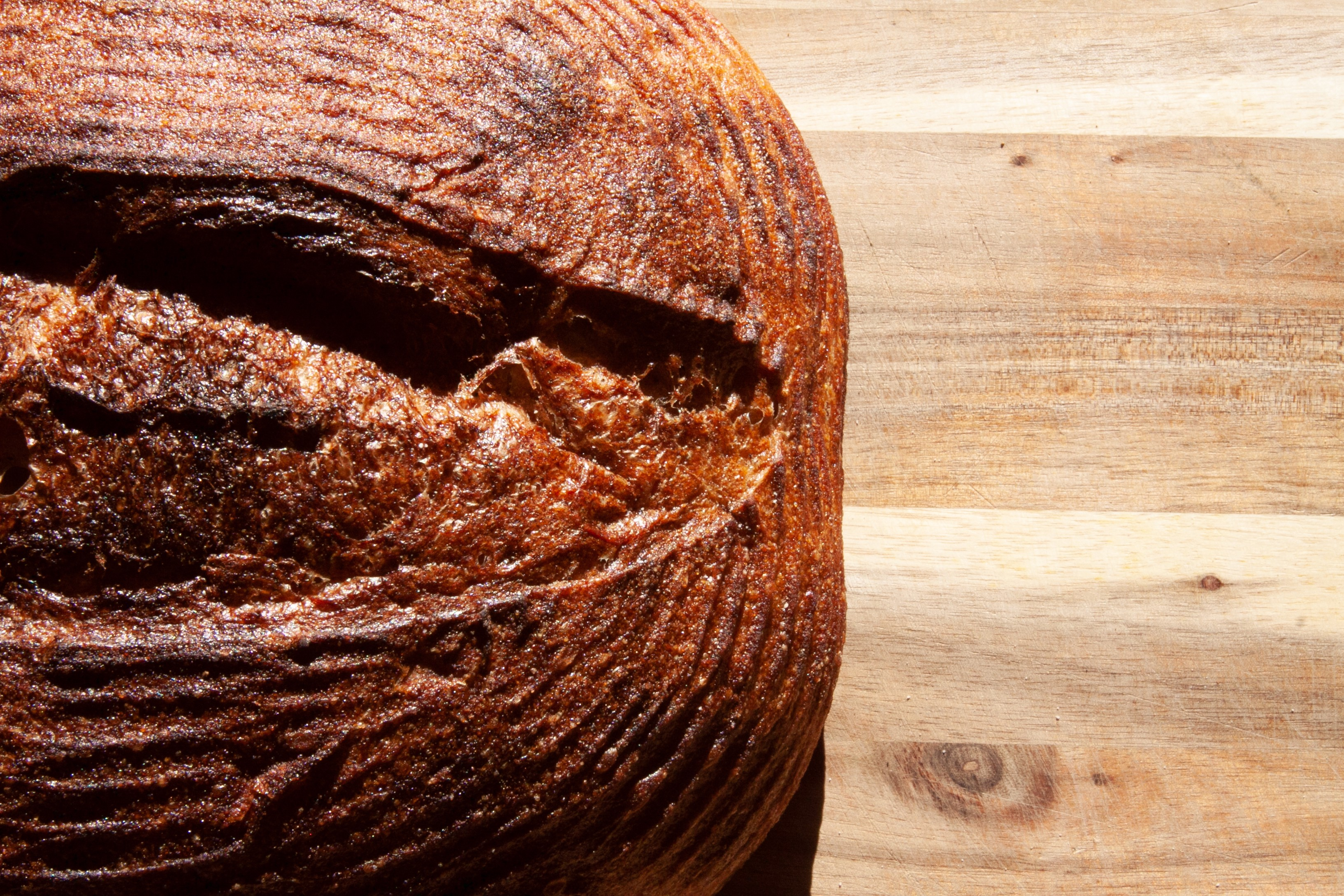 Closeup of a round, dark brown loaf of bread on a wooden surface.
