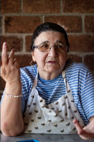 An elderly woman wearing an apron gesturing with her hand as she talks to someone off-camera.