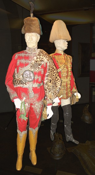 Two preserved period military dress uniforms with gold braid, ornate decorations, and tall leather boots.