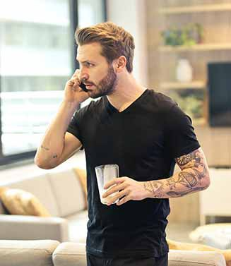 Man on the phone in his living room with a glass in his hand
