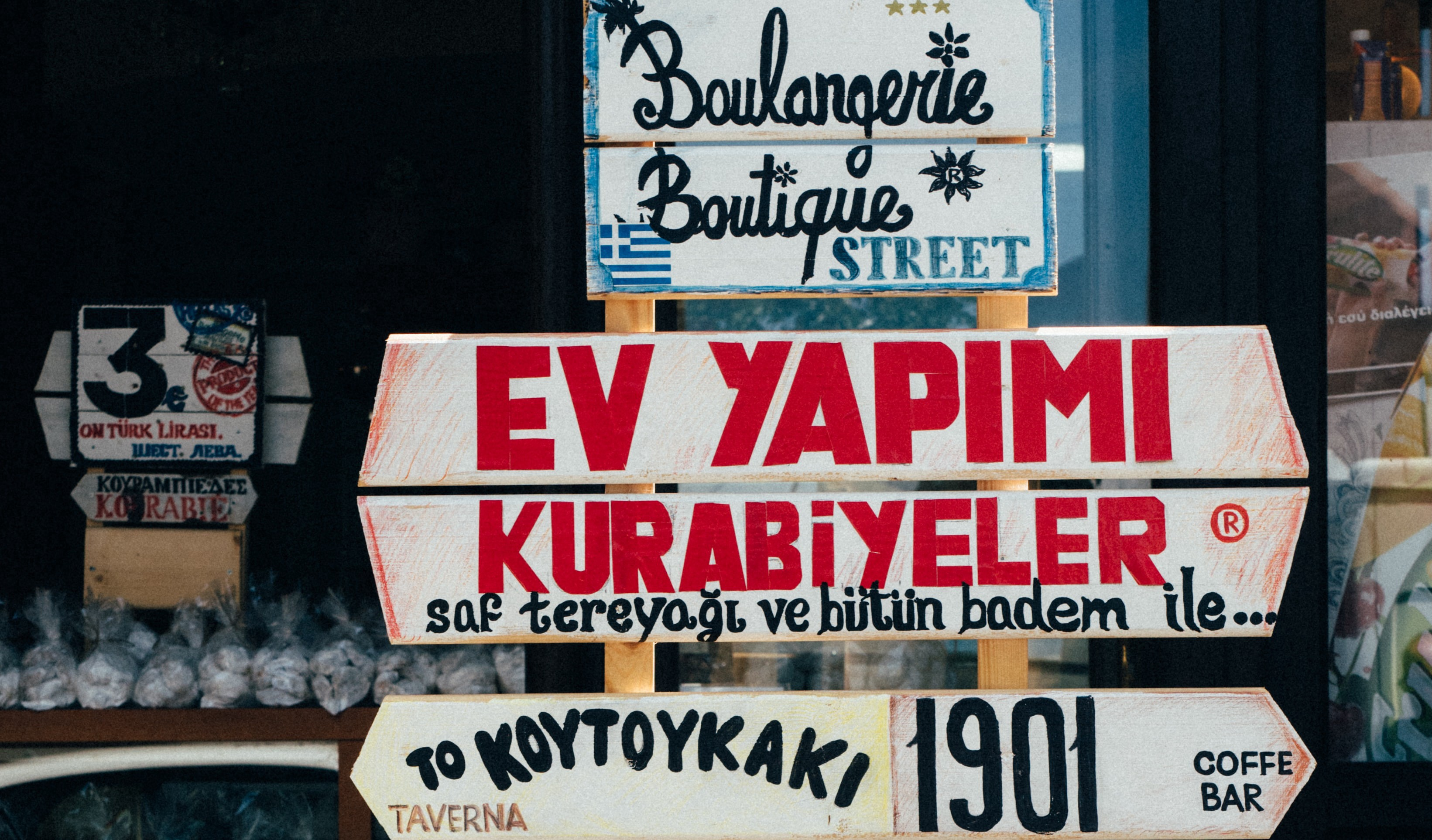 Image of a series of directional signs, with names of places and stores, in different languages such as French, Spanish, Russian, Arabic and others. Each plate has its own design, that follows a visual line, that refers to the culture of each referenced country.