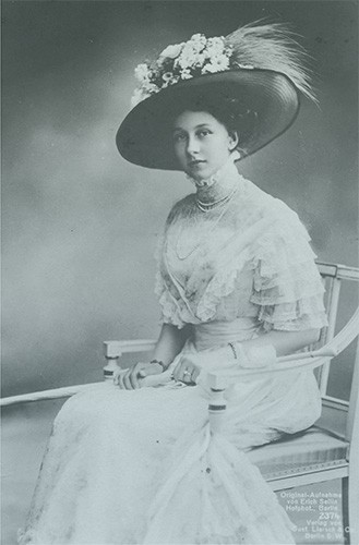 Viktoria Luise wearing a white day dress and a very large hat.