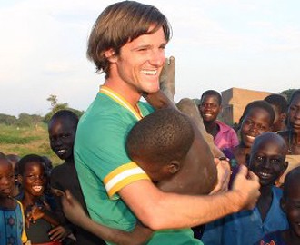 Smiling white man playfully holding a black African child as other black children look on, smiling, in the background.