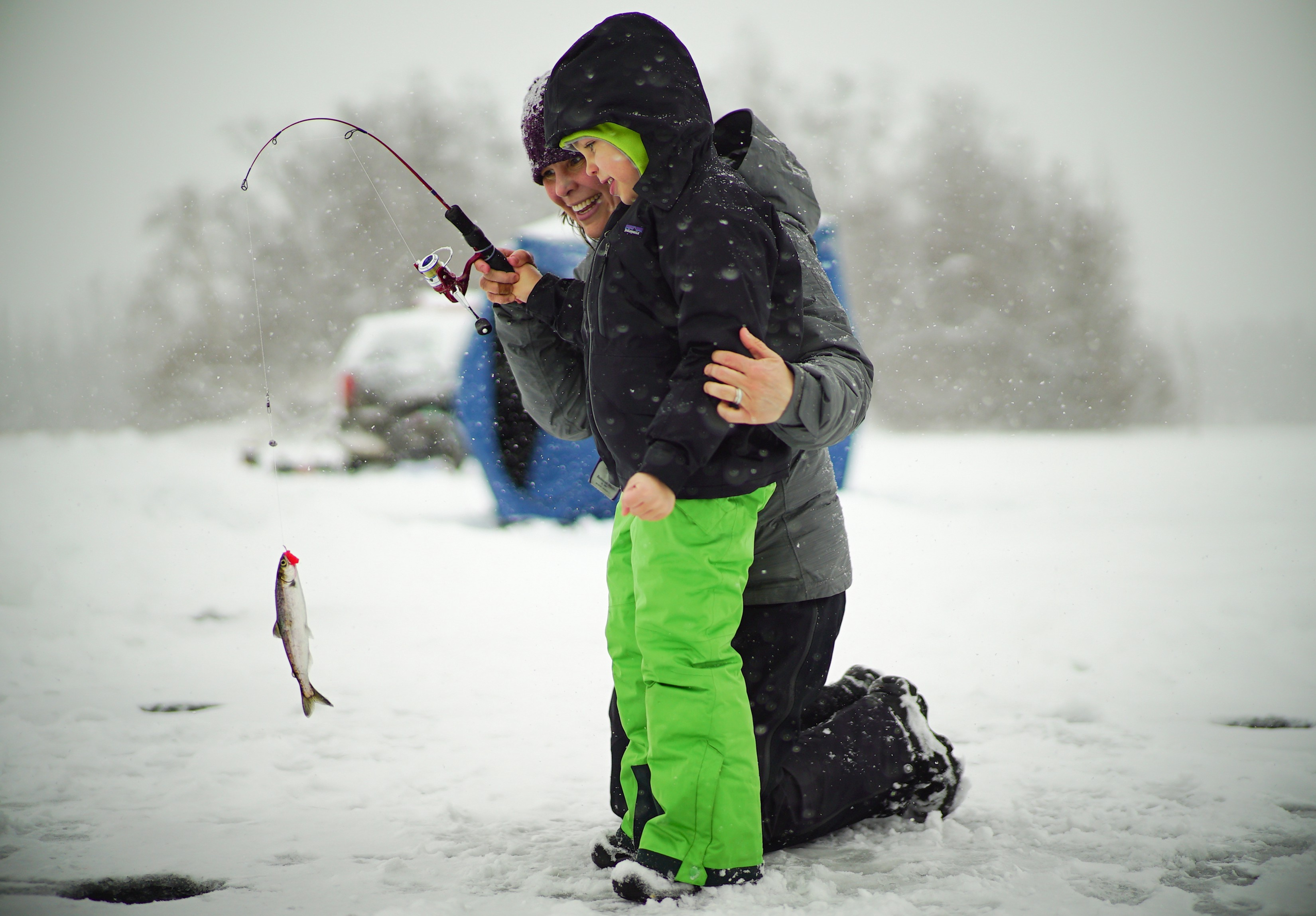 a mom ice fishing with son in Alaska
