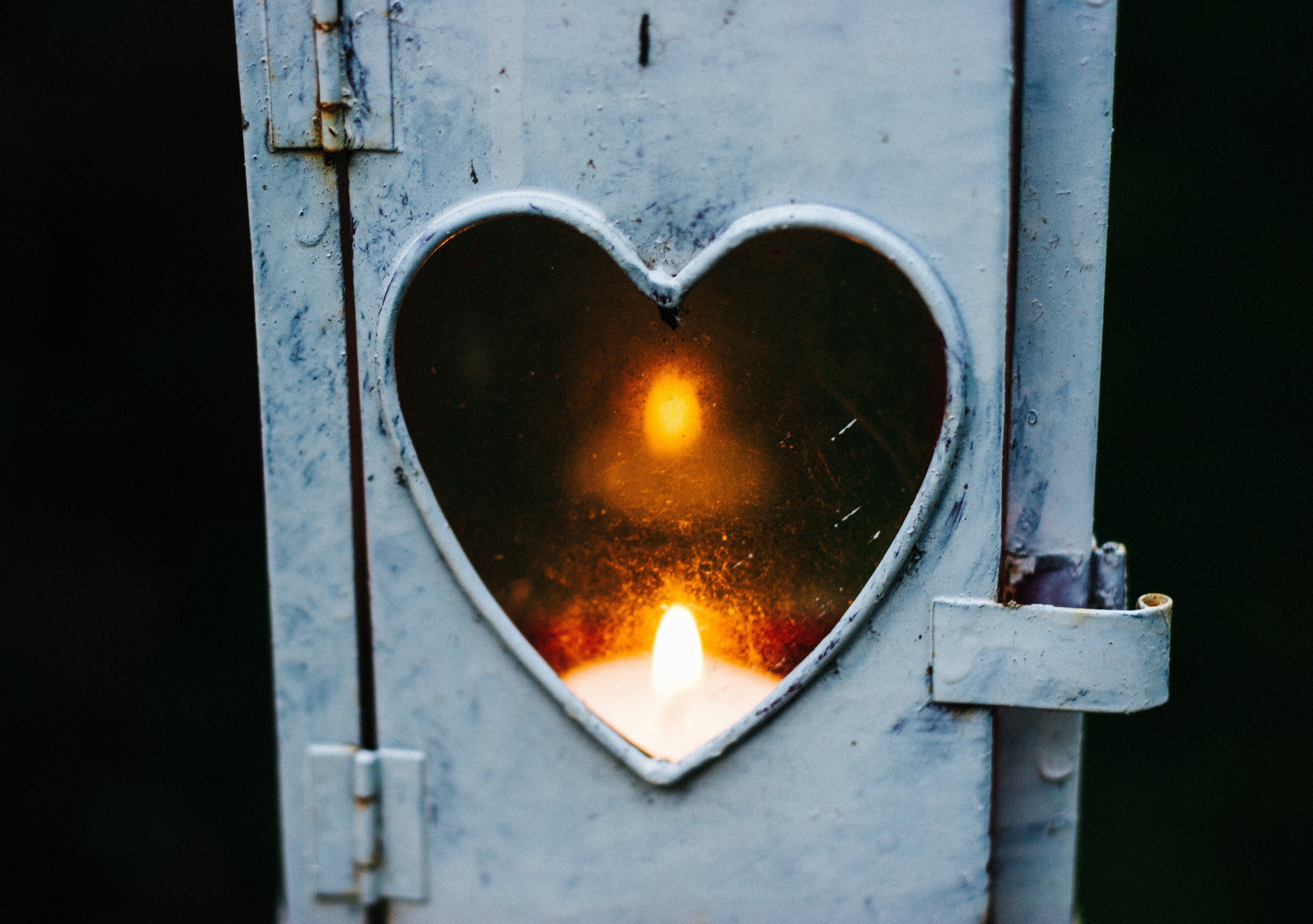 Photo of a candle in a metal container with a heart shaped window.