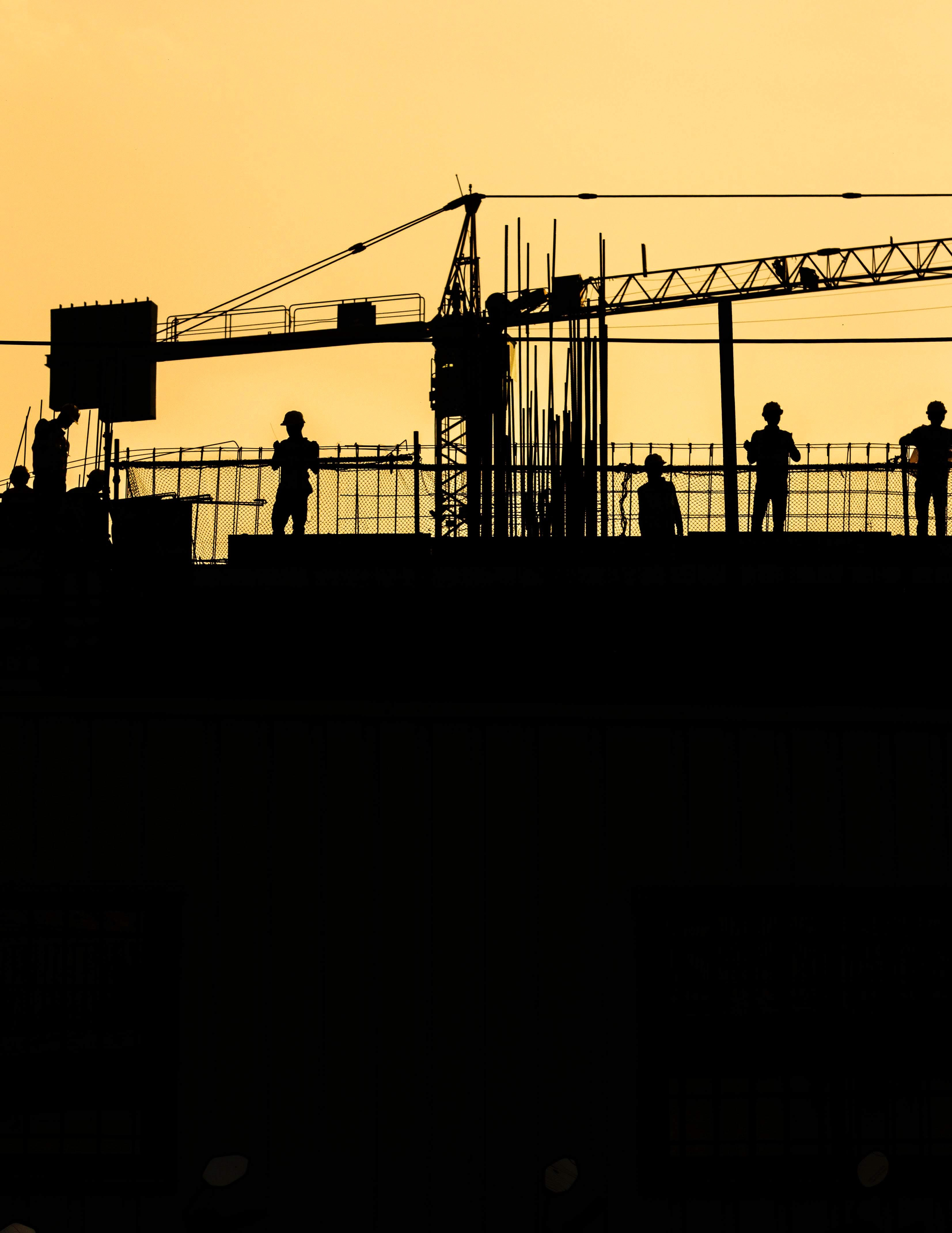Sihouette of people standing at a construction site with a crane in the background.