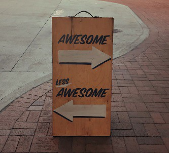 """Sign on a pavement with the word """"awesome"""" above an arrow pointing to the right, and the words """"less awesome"""" above an arrow"""