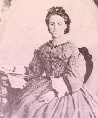 Marianne seated at a desk, reading a book. She's wearing a tightly corseted day dress in gingham or plaid.