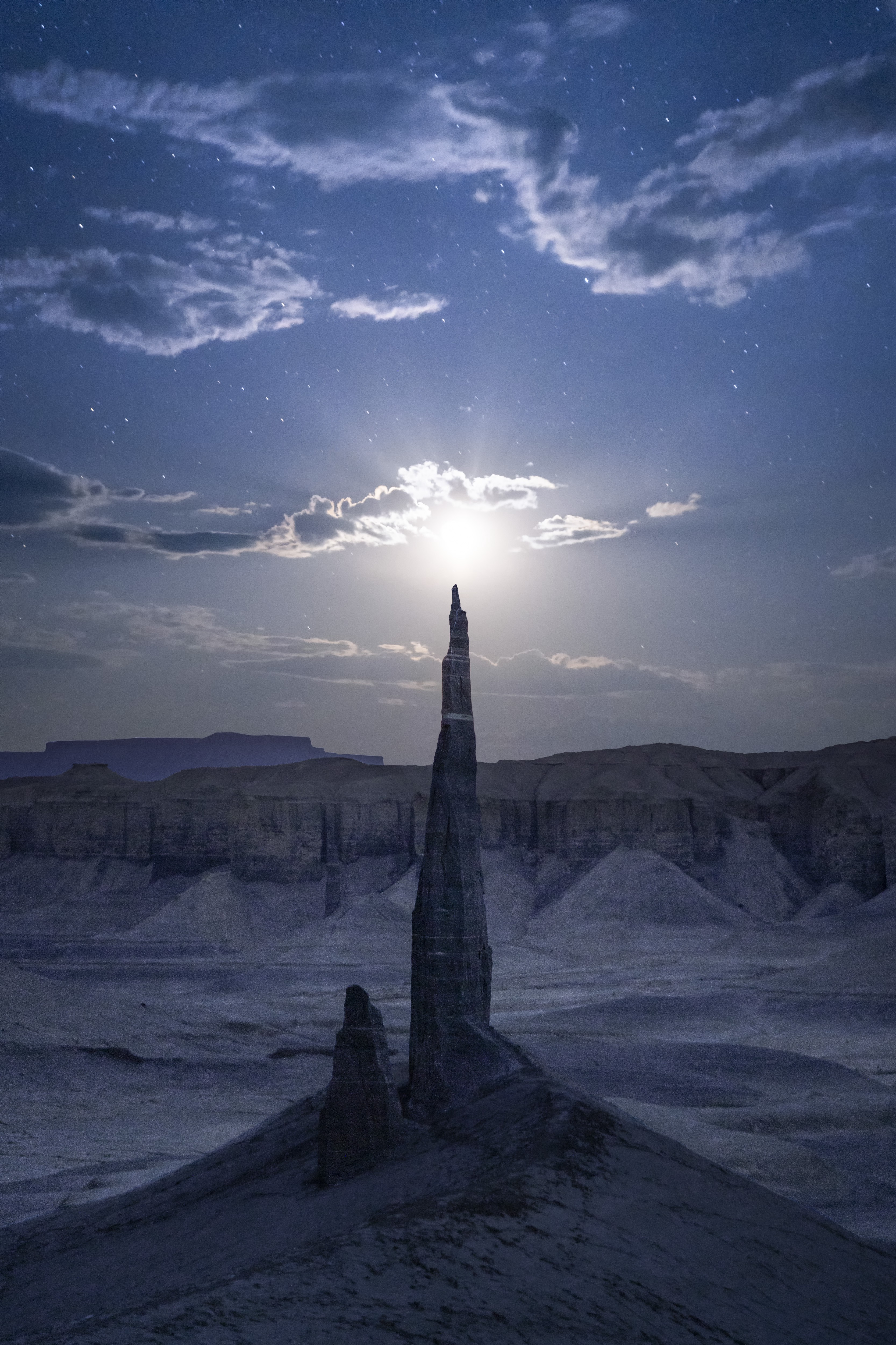 A tall natural peak seems to reach towards the glowing white sun, on a snowy landscape