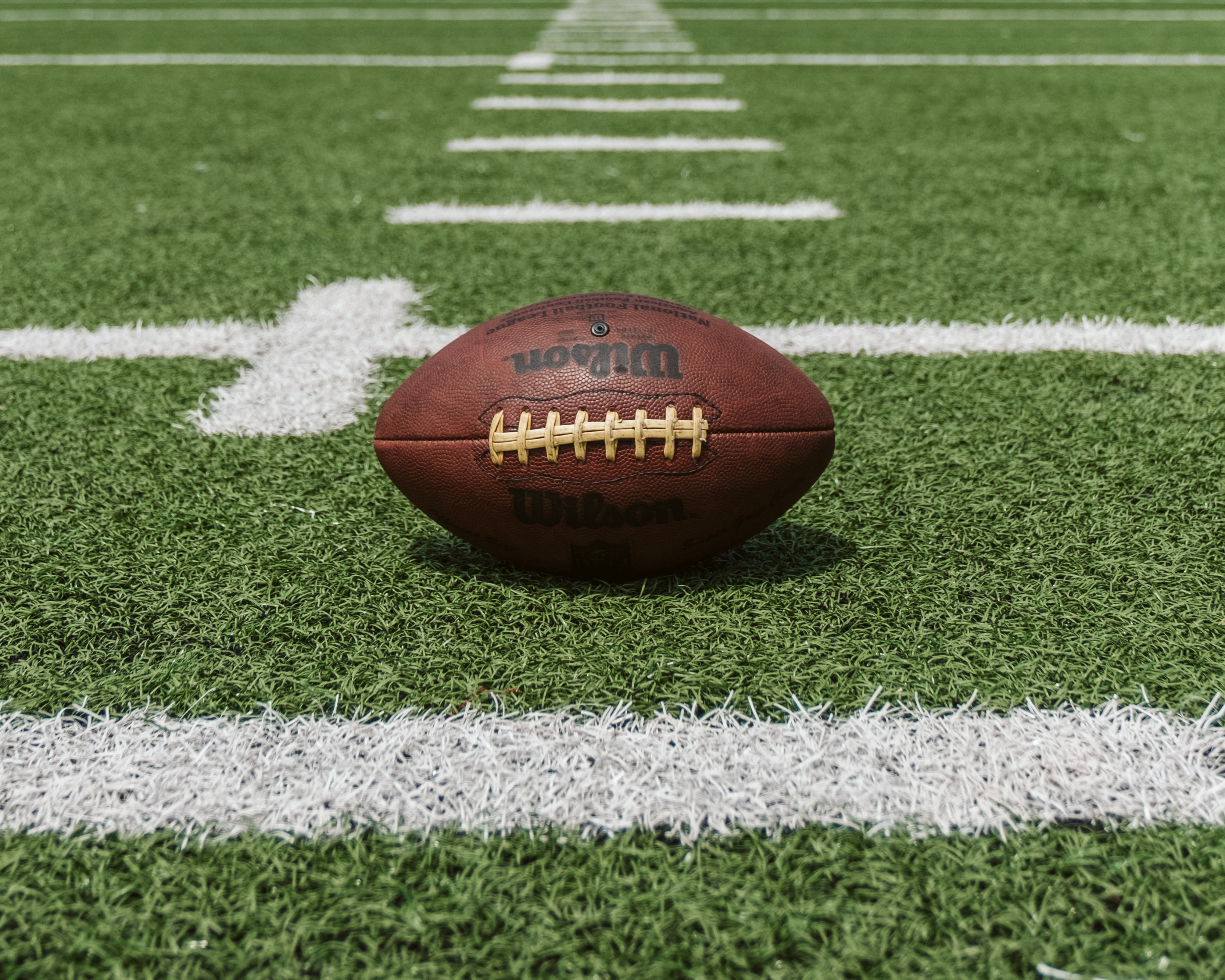 American Football laying on the field.